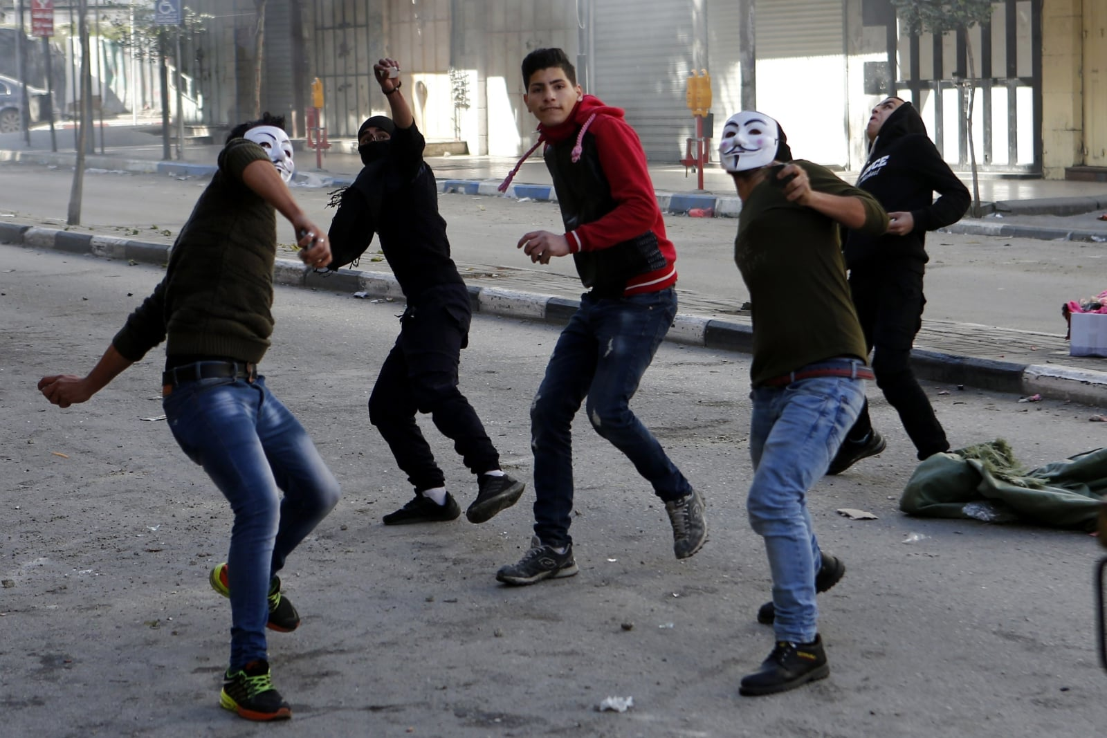 epa06492047 Palestinians hurl stones at Israeli troops during clashes in the West Bank city of Hebron, 02 February 2018. Clashes erupted as part of ongoing protests against US decision to recognize Jerusalem as the capital of Israel and US Vice President Mike Pence remarks in January that the US embassy will be relocated to Jerusalem by 2019.  EPA/ABED AL HASHLAMOUN Dostawca: PAP/EPA.