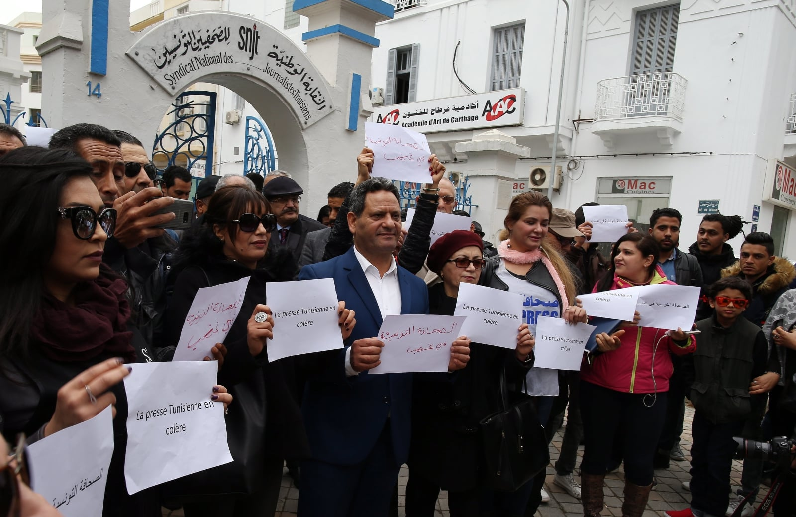 epa06492185 Tunisian journalists wearing red armbands hold signs reading in Arabic and French 'the Tunisian press is angry' during a protest outside the headquarters of the National Union of Tunisian Journalists (SNJT) in Tunis, Tunisia, 02 February 2018. According to reports, journalists gathered to protest against what they describe as 'threats and intimidation' by authorities against those covering security operations or being critical of state institutions.  EPA/MOHAMED MESSARA Dostawca: PAP/EPA.