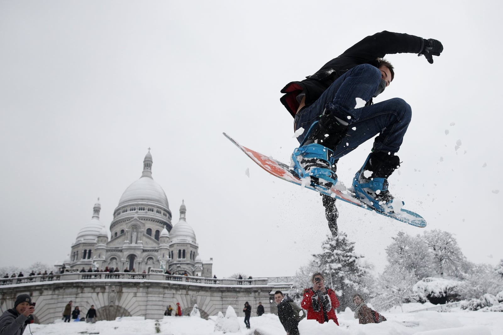 epaselect epa06502237 A man enjoys snow boarding by the Sacre Coeur basilica in Montmartre blanketed in snow, in Paris, France, 07 February 2018. Temperatures dropped with snow flurries around the capital.  EPA/YOAN VALAT Dostawca: PAP/EPA.