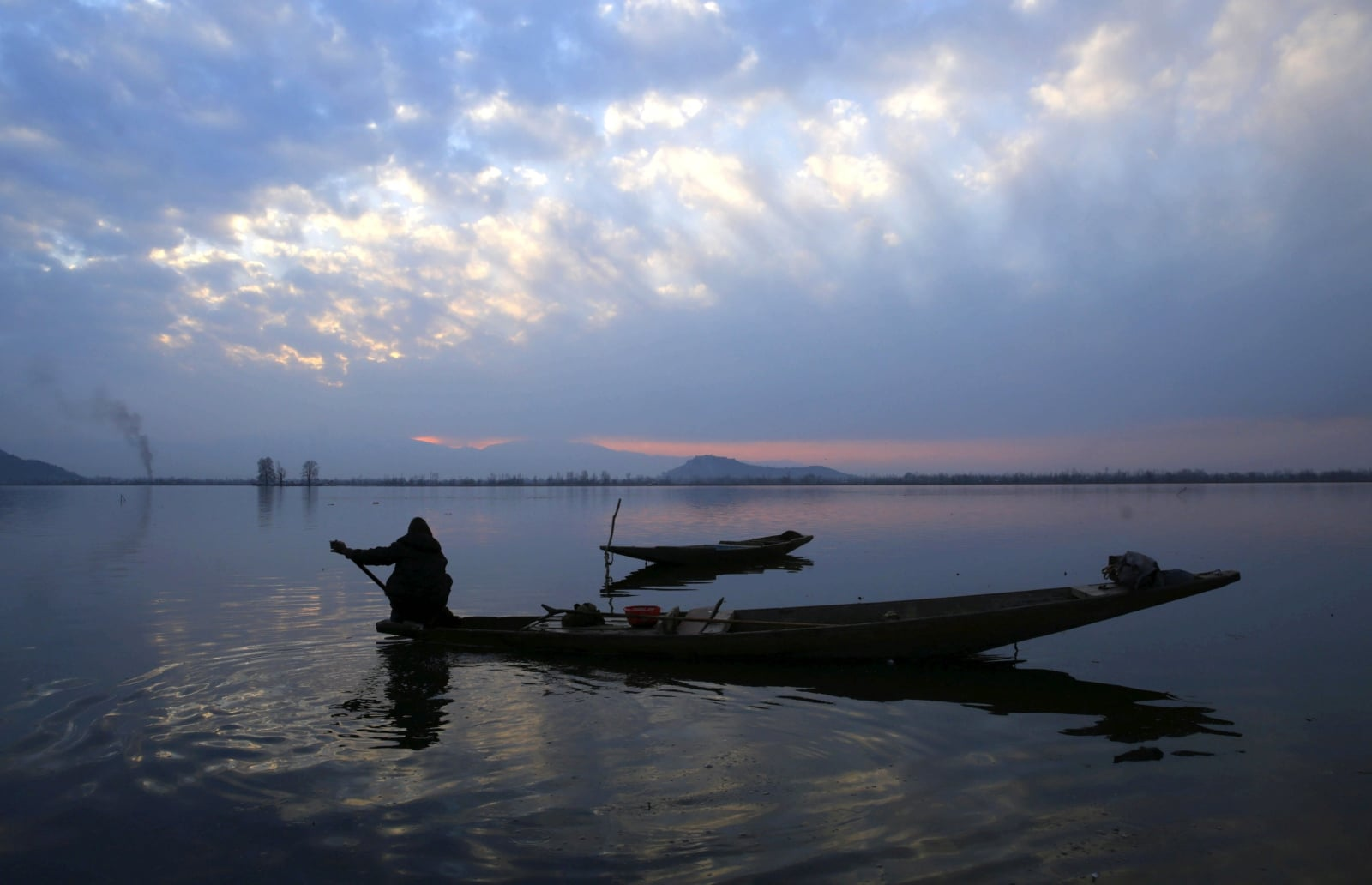 epa06502887 A Kashmiri boatman rows his boat in the waters of Dal Lake at sunset in Srinagar, the summer capital of Indian Kashmir, 07 February 2018. Kashmir continues to witness a spell of dry and cold weather with warm day time temperatures and cold night temperatures.  EPA/FAROOQ KHAN Dostawca: PAP/EPA.