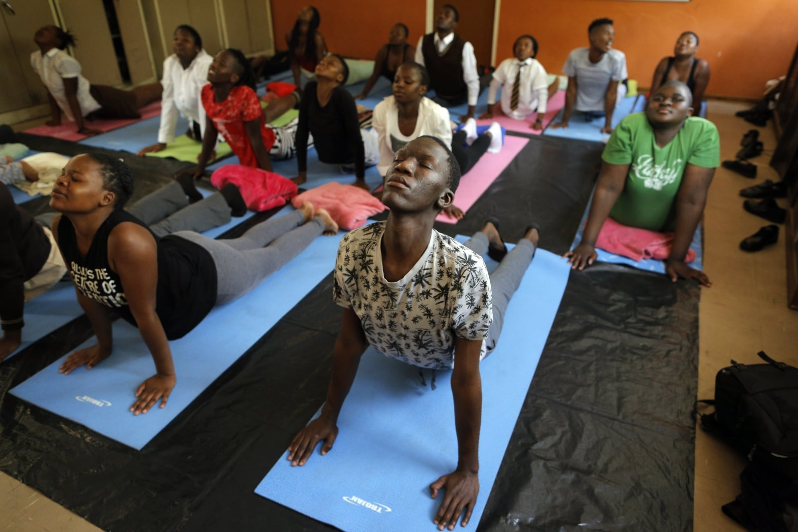 epa06503355 (05/25) School children at the Minerva Secondary School do 'upward facing dog' yoga pose during their afternoon yoga class taught by Yoga4Alex teachers in Alex Township, Johannesburg, South Africa, 01 November 2017. The NGO Yoga4Alex is bringing the ancient India spiritual practice of Kundalini Yoga to the school children of this impoverished area of the city. The aim of Yoga4Alex is to ultimately help the learners reach their personal goals and their full potential by bringing stability into their lives.  Alexandra township or 'Alex' as it is known to dwellers in the urban living area - is one of the main townships on the edges of the capital and was built in the early 1900s to house non-white residents.  EPA/KIM LUDBROOK   ATTENTION: For the full PHOTO ESSAY text please see Advisory Notice epa06503350 Dostawca: PAP/EPA.