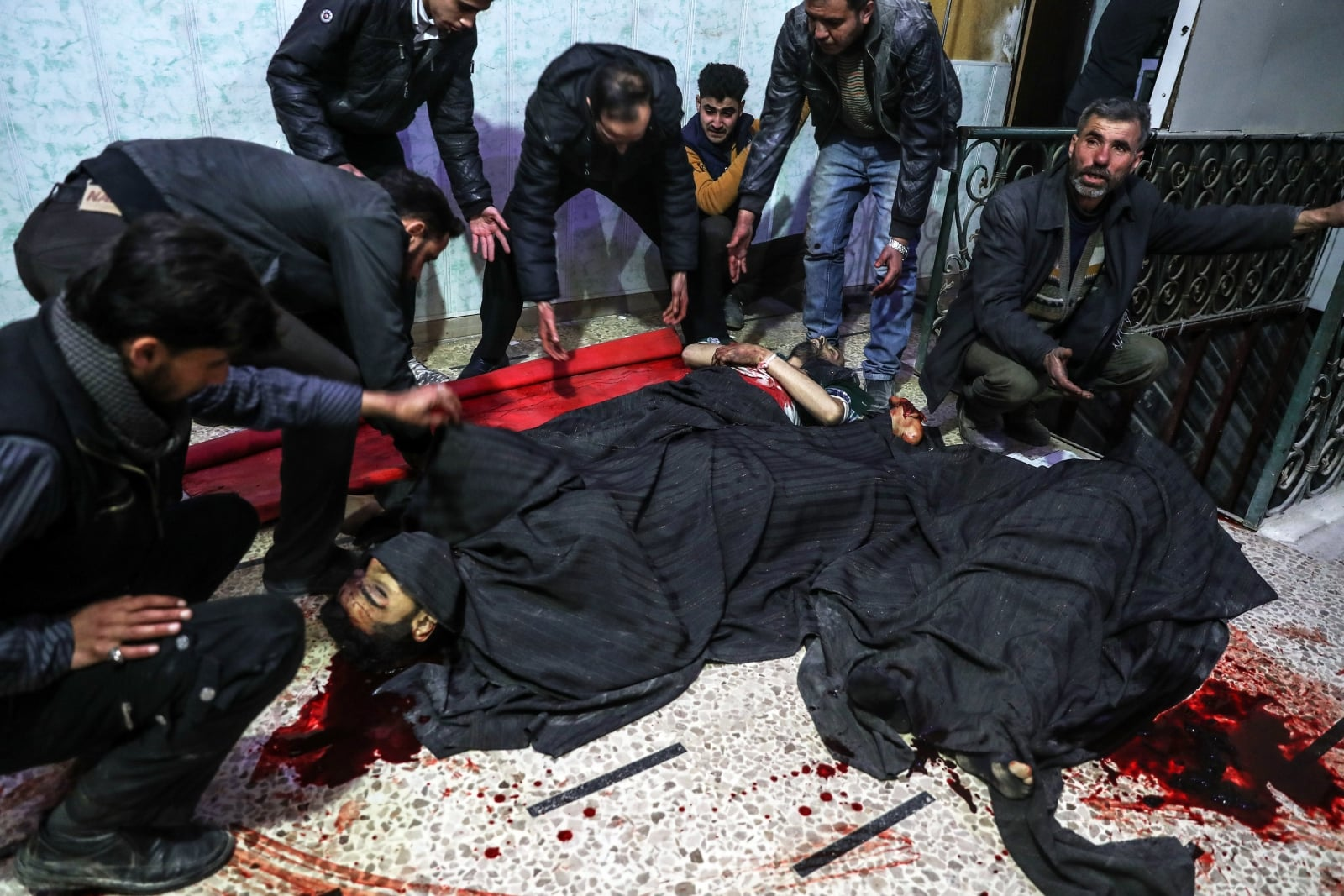 epa06503641 People react as they gather around bodies of people killed in bombings in Douma in a hospital in Douma, eastern Ghouta, Syria, 07 February 2018. More than 12 people were killed today after bombings carried out by forces loyal to Syrian goverment in Douma and more than 36 people were killed in the whole Eastern al-Ghouta cities.  EPA/MOHAMMED BADRA ATTENTION EDITORS: PICTURE CONTAINS GRAPHIC CONTENT Dostawca: PAP/EPA.