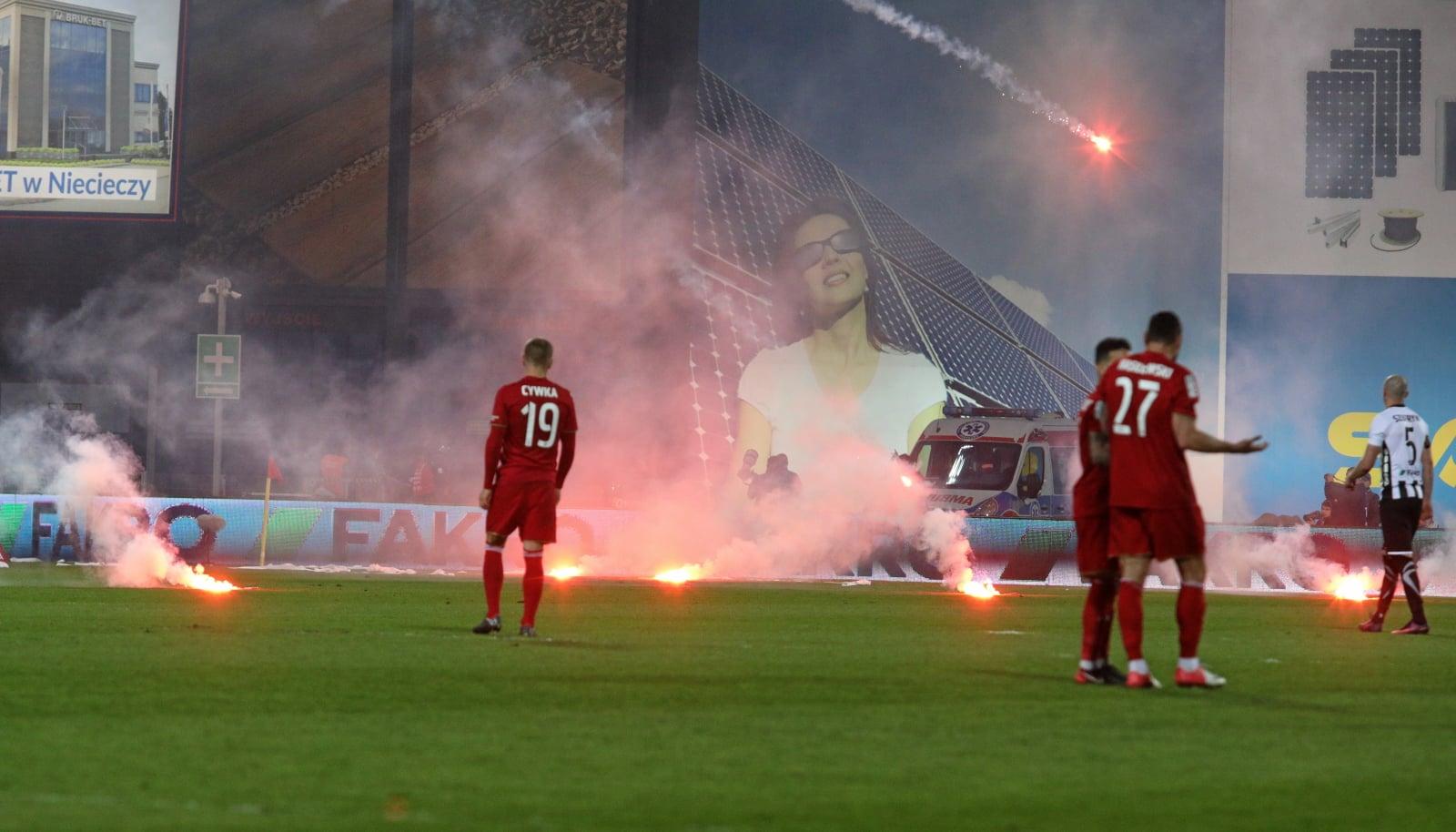 Kibice Sandecji Nowy Sącz rzucają race podczas meczu piłkarskiej Ekstraklasy z Wisłą Kraków.