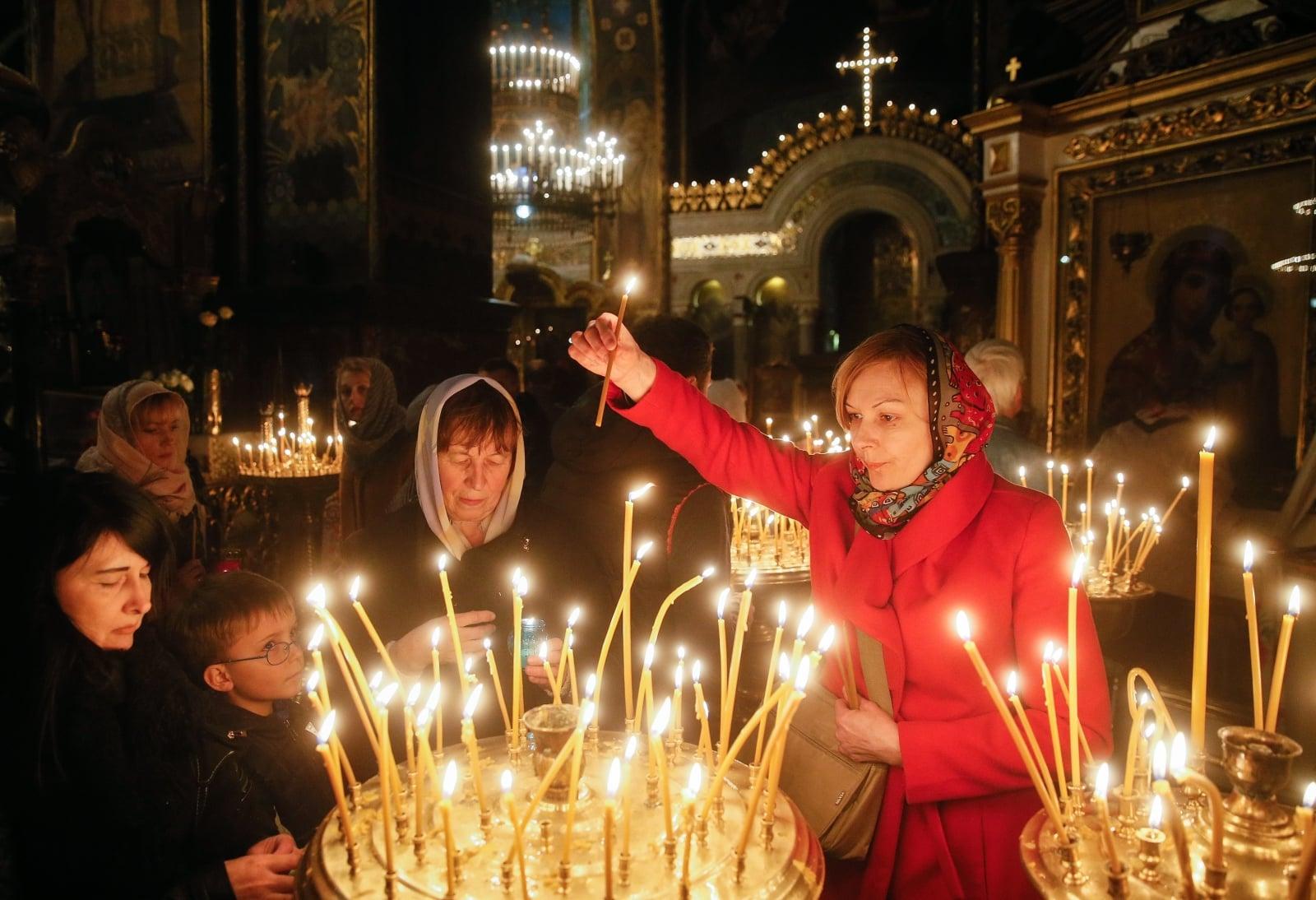 Wierni prawosławni zapalają świece w czasie Mszy wigilijnej, Kijów, Ukraina.