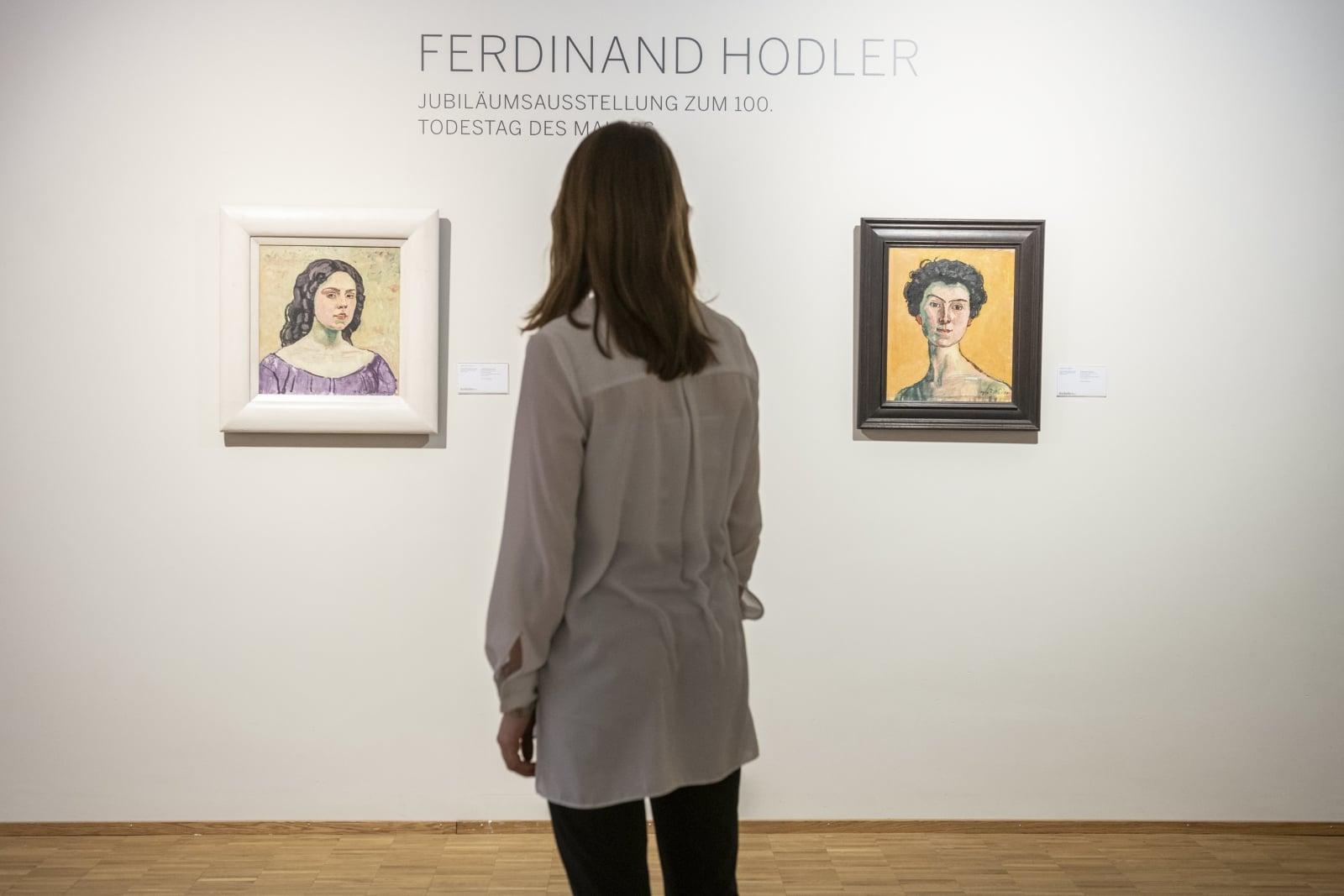 Kobieta patrzy na obrazy w czasie wystawy dzieł malarza Ferdinanda Hodlera w Zurichu, Szwajcaria.