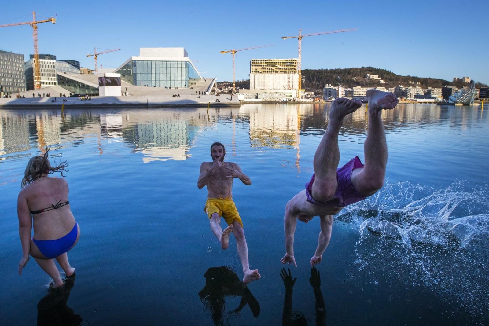 Norwegowie skaczą do zimnego morza na zewnątrz Opery, Oslo, Norwegia.
