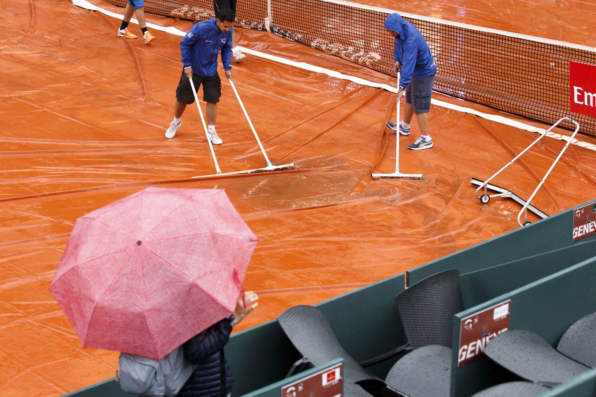 Szwajcaria, Genewa: personel usuwa wodę z osłony przeciwdeszczowej centralnego sądu przed drugą rundą meczu podczas turnieju Geneva Open, fot: Salvatore Di Nolfi, PAP/EPA