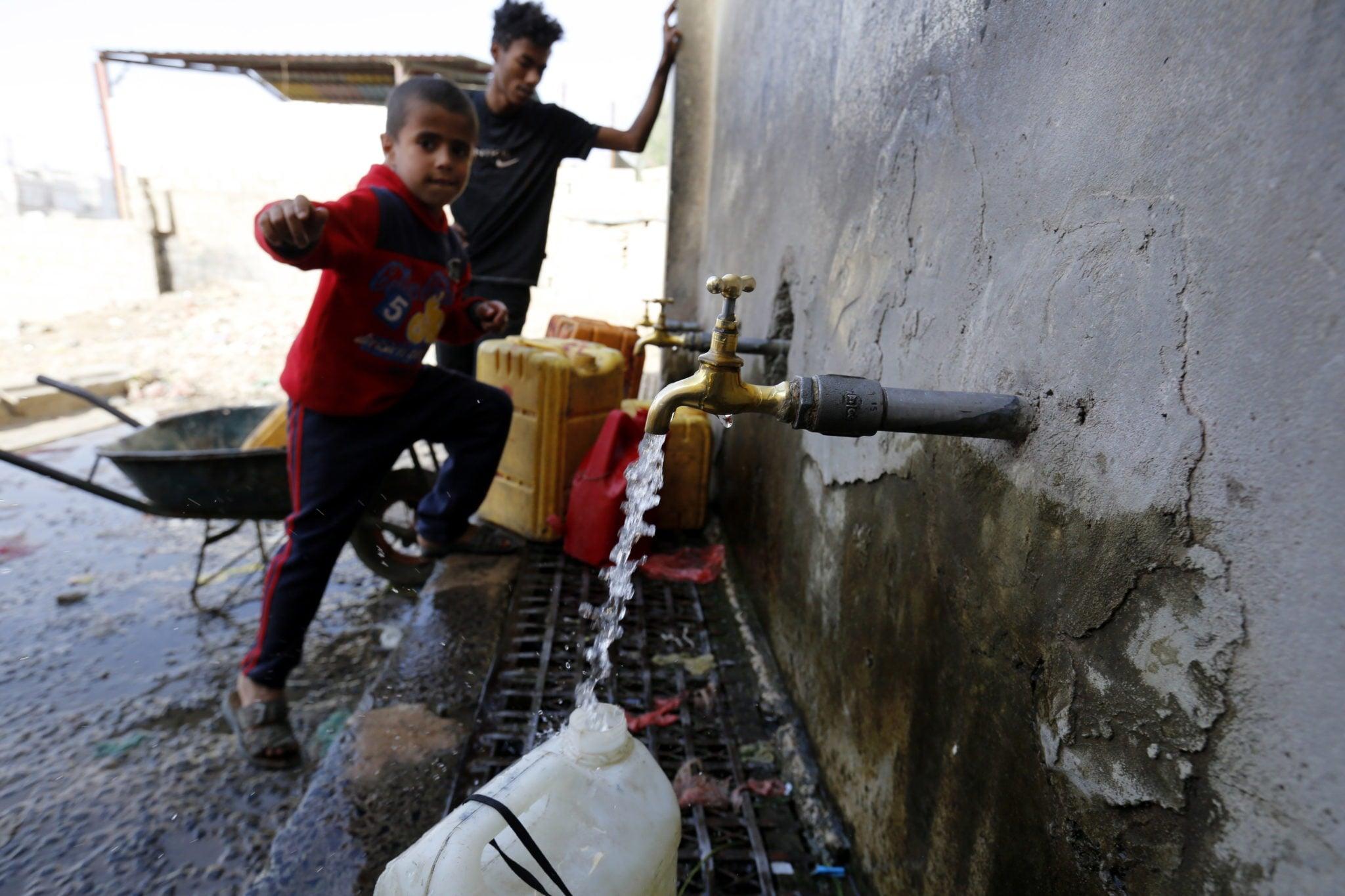 Jemeńskie dzieci nabierają pitną wodę do pojemników w Sanie, stolicy kraju, fot: Yahya Arhab, PAP/EPA