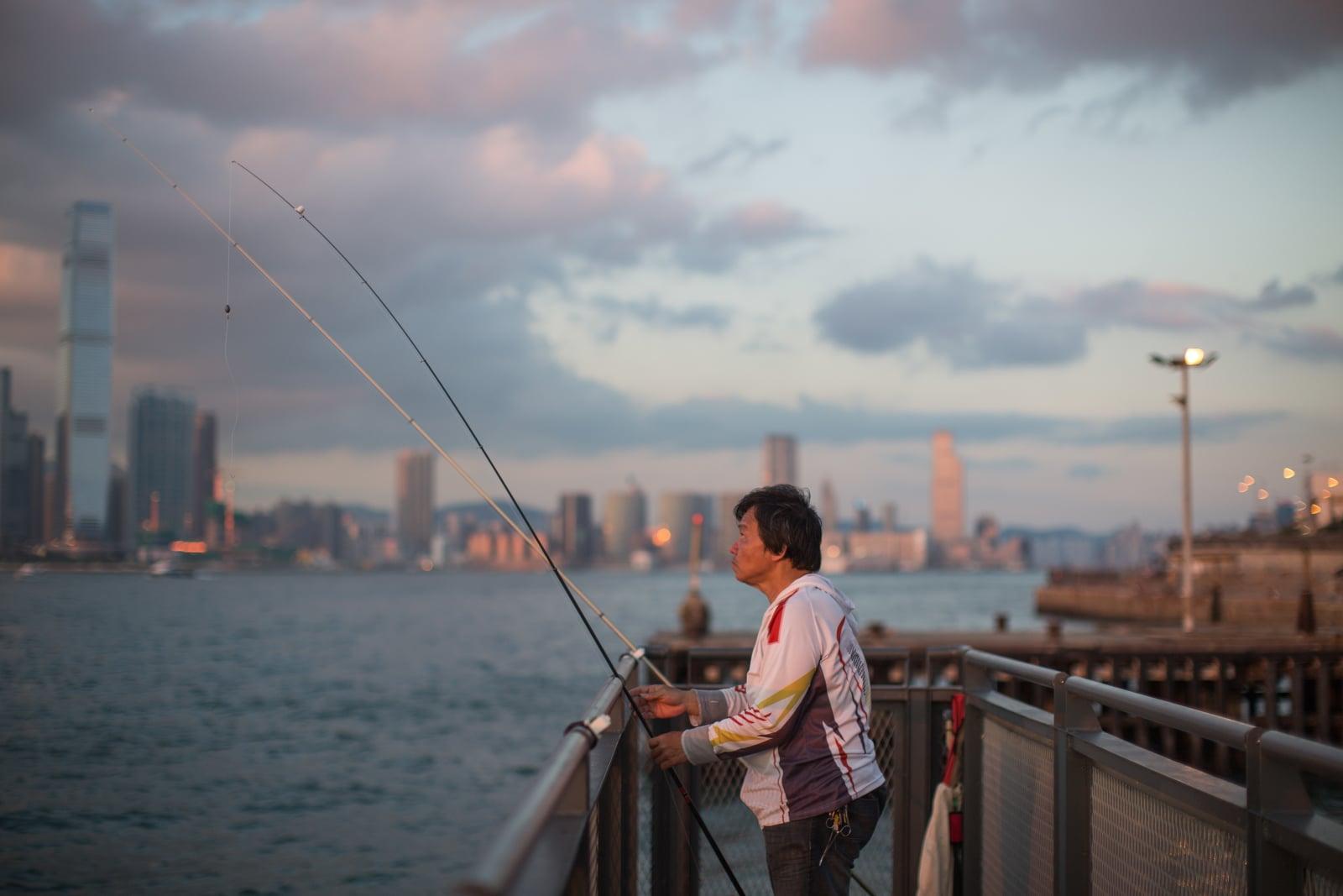 Rybak na molo o zachodzie słońca w Victoria Harbour w Hongkongu, fot. EPA/JEROME FAVRE