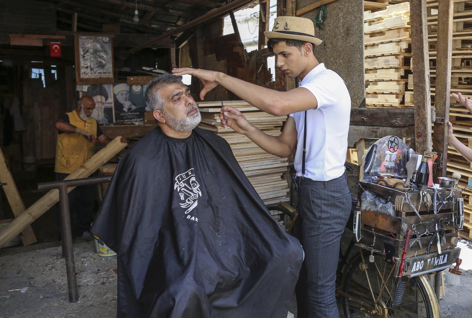 Libańczyk Mohammed Jahjah, który pracuje jako wędrowny barber, goli brodę swojemu klientowi na ulicy w obozie dla uchodźców w Bourj al-Barajneh, południowe przedmieścia Bejrutu, Liban, fot. EPA/NABIL MOUNZER