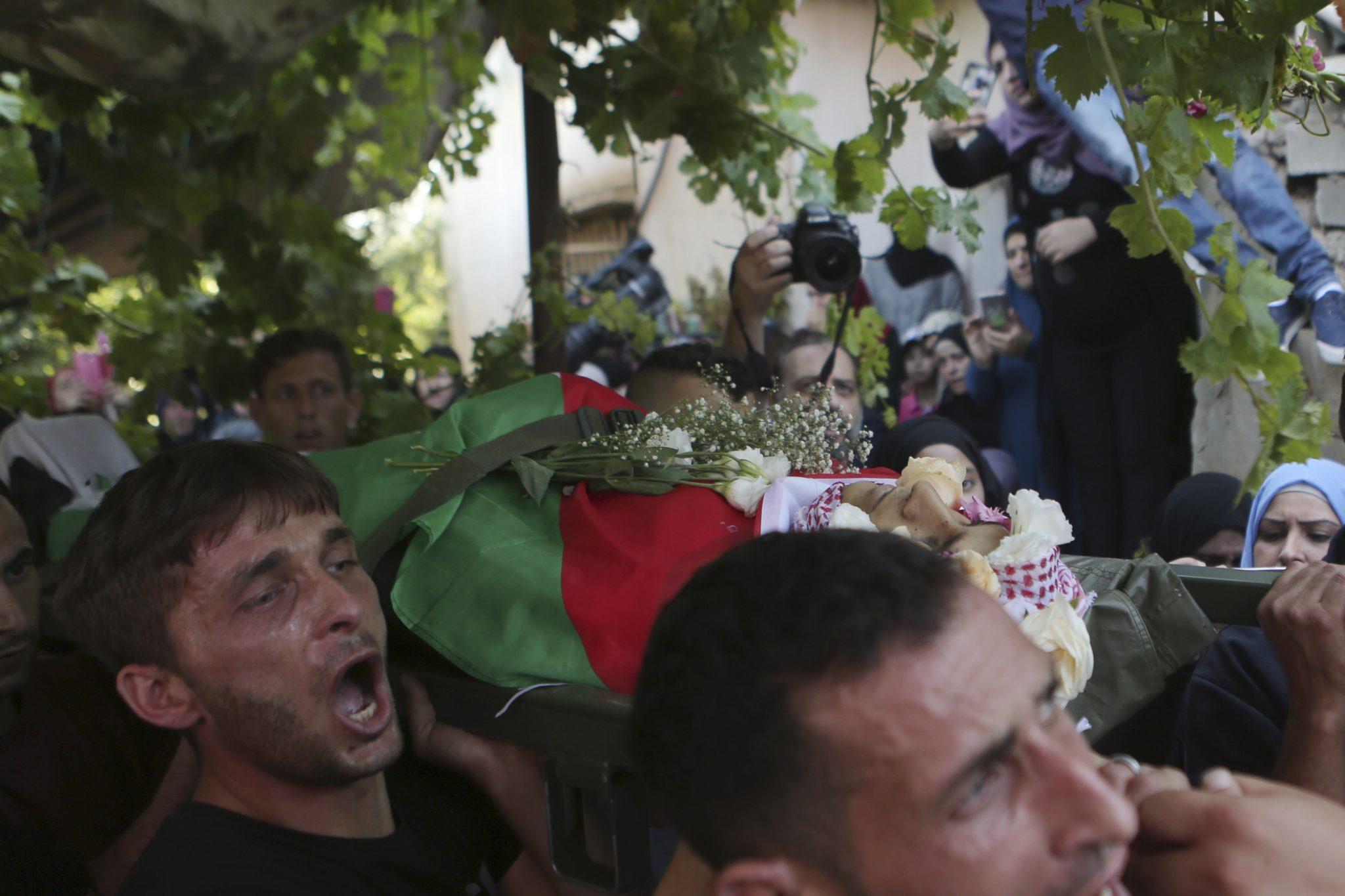 Palestyna: krewni i członkowie rodziny uczestniczą w pogrzebie 21-letniego Ezz El-Deen al-Tamimi w wiosce Nabi Saleh na Zachodnim Brzegu. Mężczyzna zginął w czasie walk Palestyńczyków z siłami izraelskimi, które toczą się od wielu tygodni, fot: Shadi Hatem, PAP/EPA