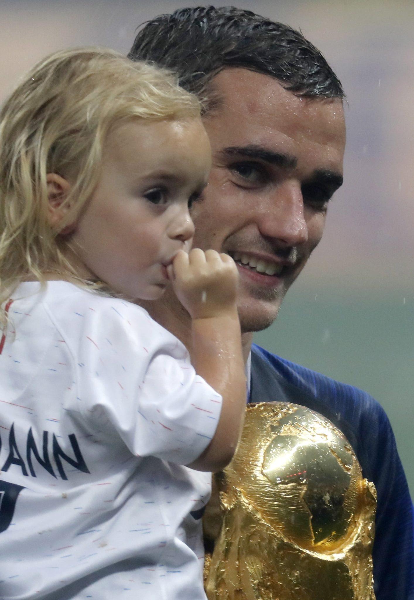 Antoine Griezmann - piłkarz reprezentacji Francji - z Pucharem Świata i ze swoją córką Mią, fot. Felipe Trueba, PAP/EPA