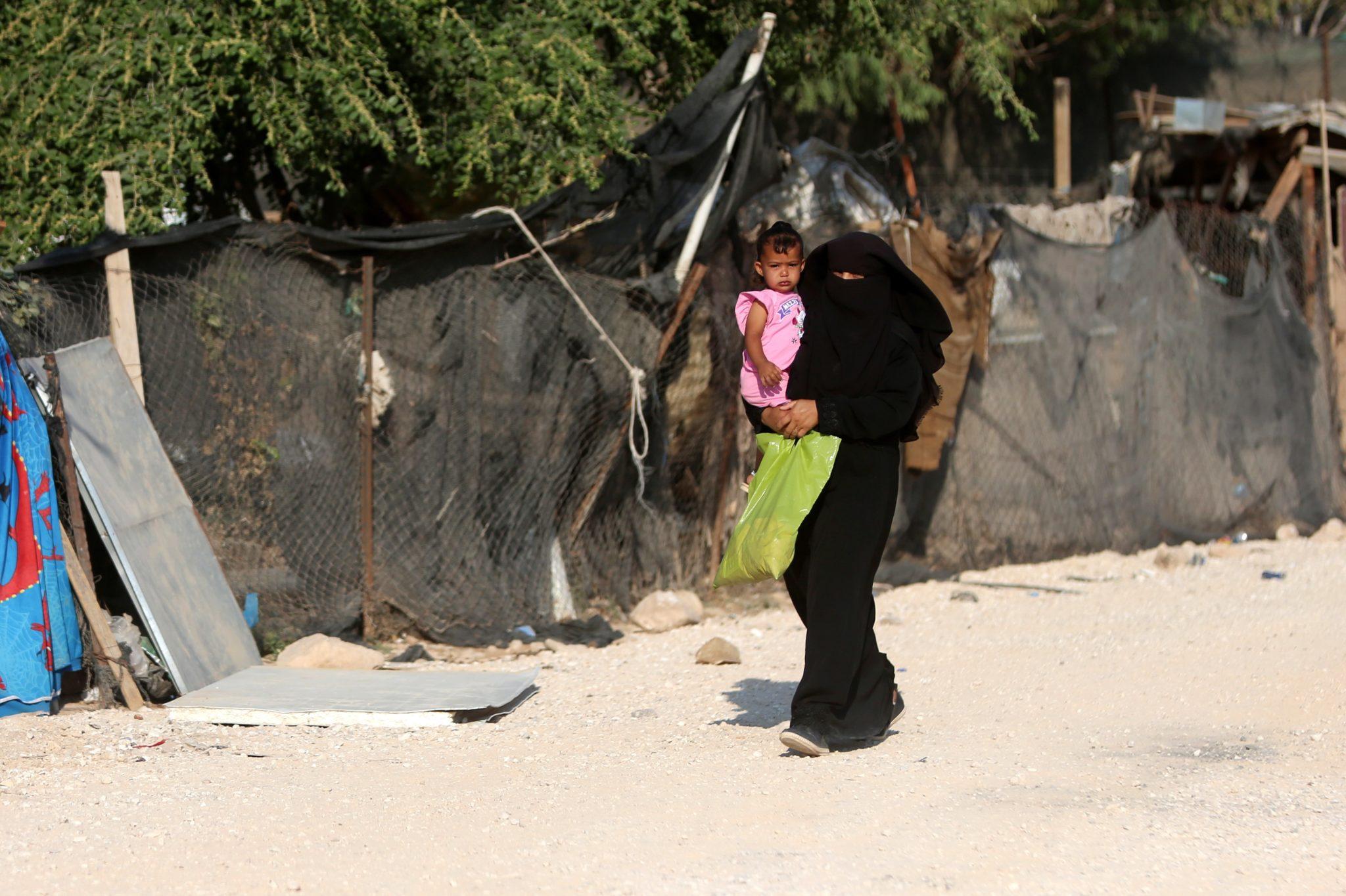 Beduińska kobieta nosi córkę pierwszego dnia nowego roku szkolnego w beduińskiej społeczności Khan al-Ahmar, położonej pomiędzy miastem Jerycho i Jerozolimą, w pobliżu izraelskiej osady Maale Adumi, fot. Shadi Hatem, PAP/EPA