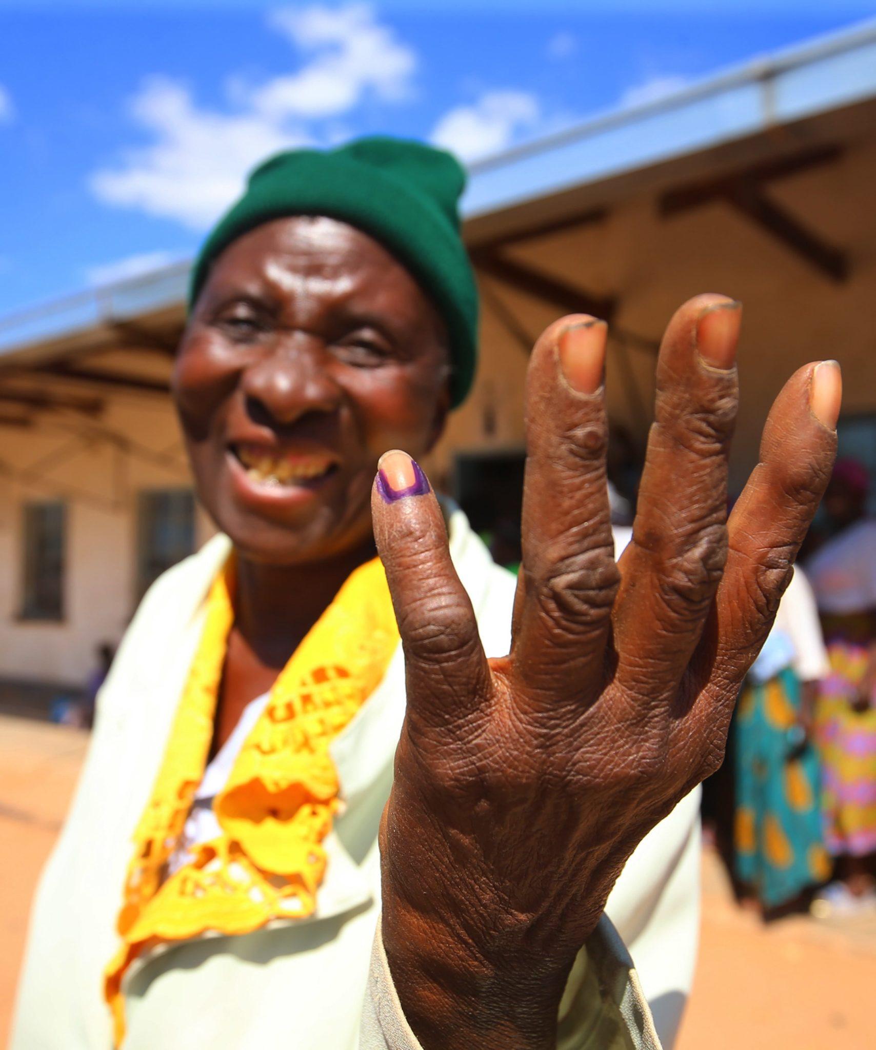 Starsza kobieta pokazuje, że jej mały palec jest oznaczony markerem atramentu po tym, jak oddała swój głos w wyborach, fot. Aaron Ufumeli, PAP/EPA // W Zimbabwe zakończyły się w poniedziałek wybory prezydenckie i parlamentarne, pierwsze po odsunięciu od władzy dyktatora Roberta Mugabego. To historyczne głosowanie.
