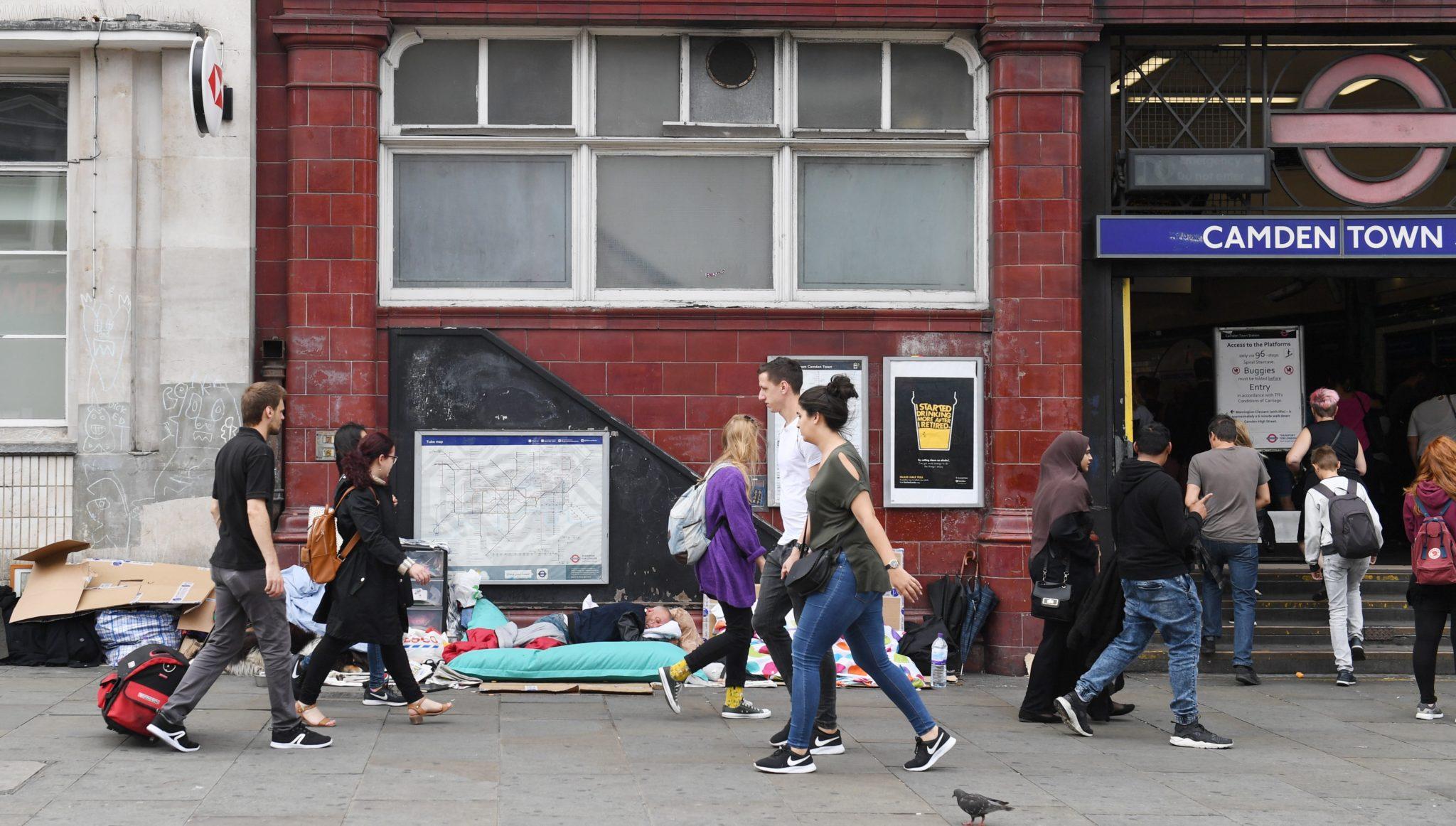 Piesi przechodzą obok bezdomnego śpiącego przy wejściu do stacji metra Camden Town w Londynie, fot. Facundo Arrizabalaga, PAP/EPA