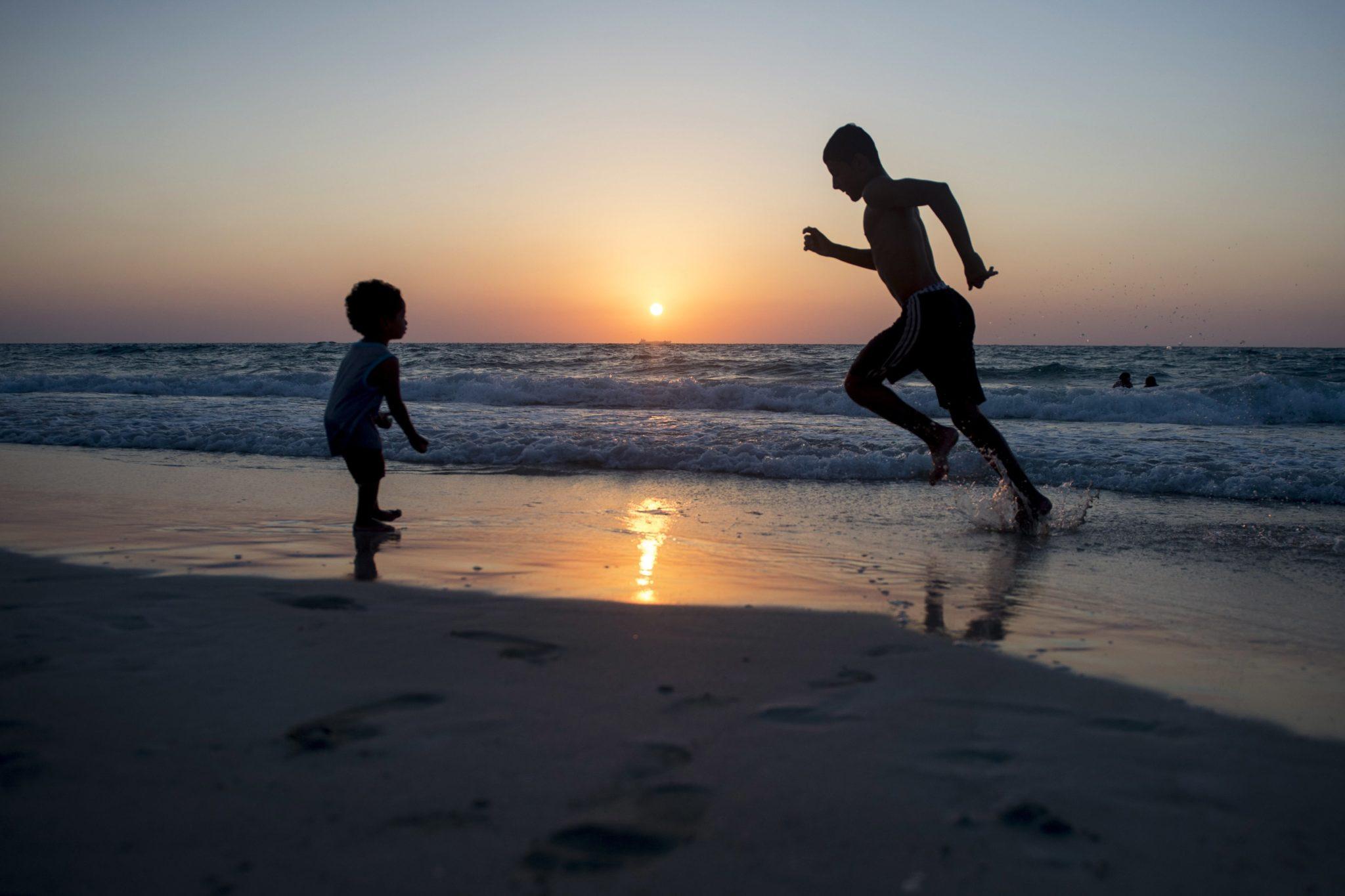 Egipt, Aleksandria. Egipski chłopiec biegnie na plaży o zachodzie słońca na północnym wybrzeżu Morza Śródziemnego, fot. Mohamed Hossam, PAP/EPA