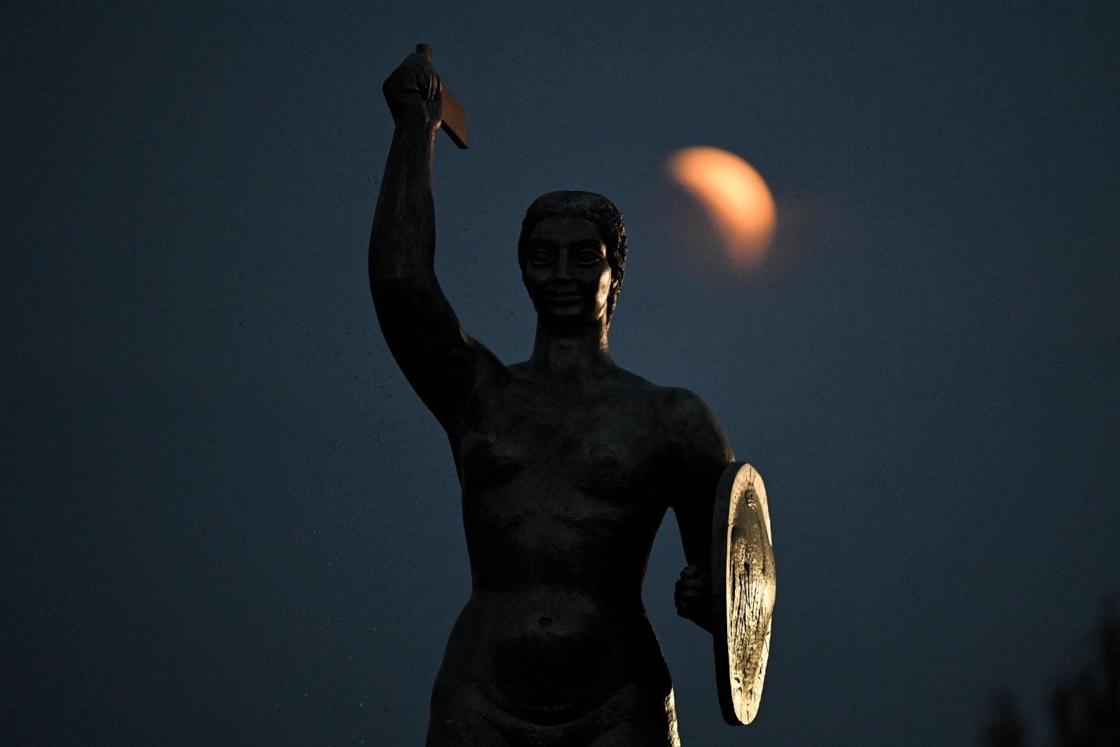 Początkowa faza zaćmienia księżyca obserwowana przed Pomnikiem Syrenki w Warszawie, fot. PAP/Radek Pietruszka