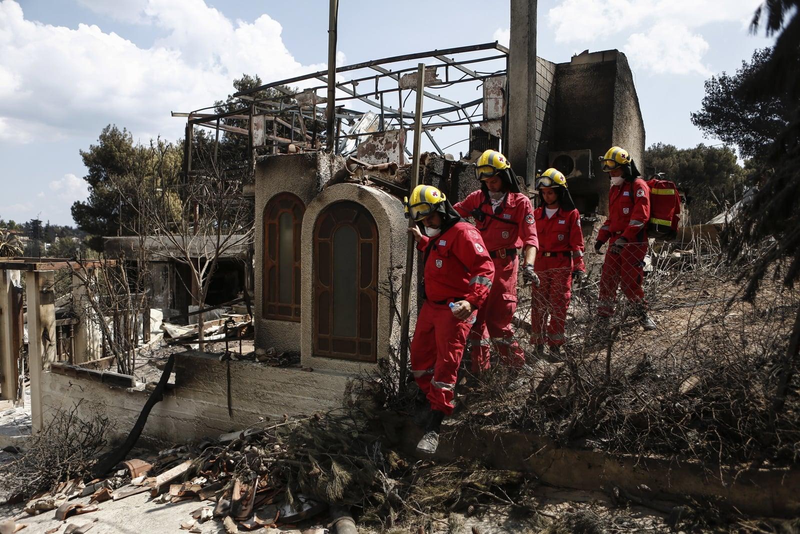 Członkowie greckiego Czerwonego Krzyża szukają zaginionych osób w spalonym domu, po śmiertelnym pożarze lasu w Mati na północnym przedmieściu Aten, fot. EPA/YANNIS KOLESIDIS
