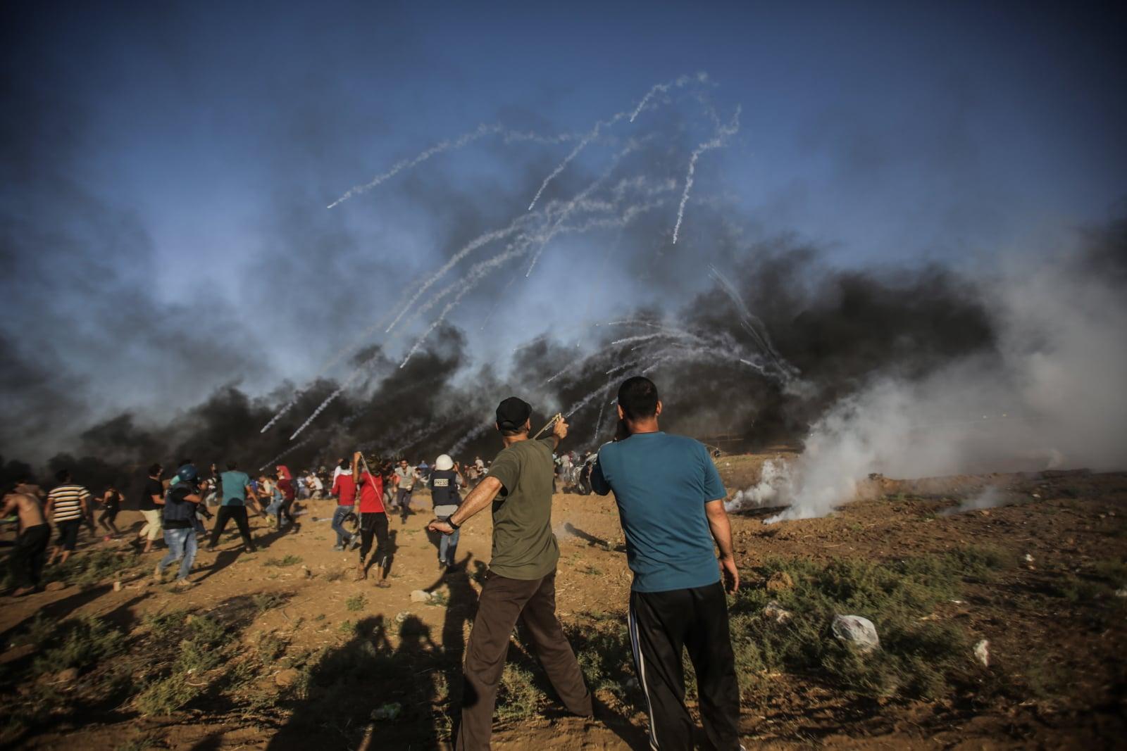 Protestujący Palestyńczycy uciekają przed izraelskim gazem łzawiącym podczas starć z izraelskimi oddziałami w pobliżu granicy z Izraelem we wschodniej Strefie Gazy, fot. EPA/HAITHAM IMAD