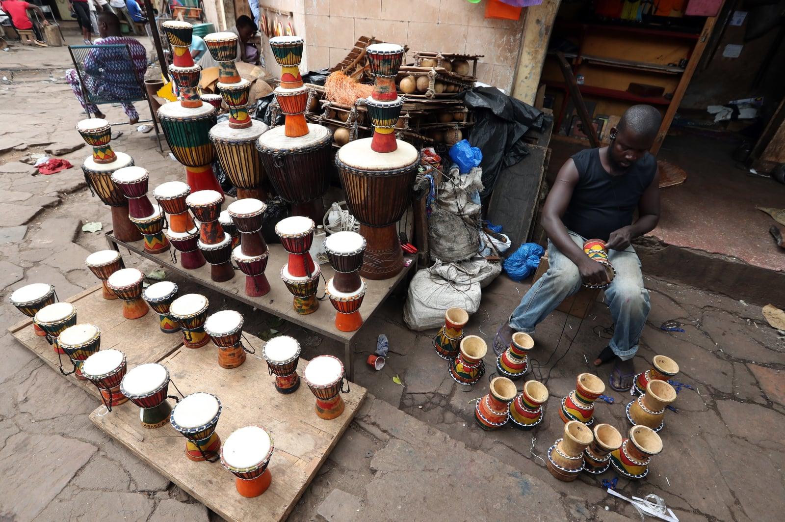 Malijczyk produkujący afrykański instrument perkusyjny, na rynku Bamako, Mali, fot. EPA/MOHAMED MESSARA