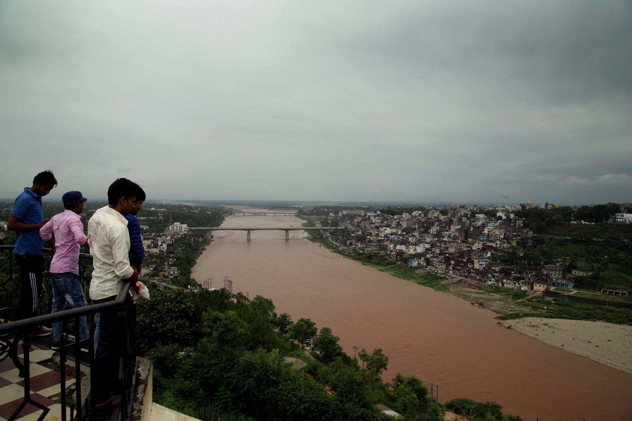 Mieszkańcy Indii spoglądają na wezbrane wody rzeki. Stan wód podnosi się po przejściu monsunowych opadów. Początek monsunu zwykle rozpoczyna się w Indiach na początku czerwca i kończy się we wrześniu, fot. Jaipal Singh, PAP/EPA