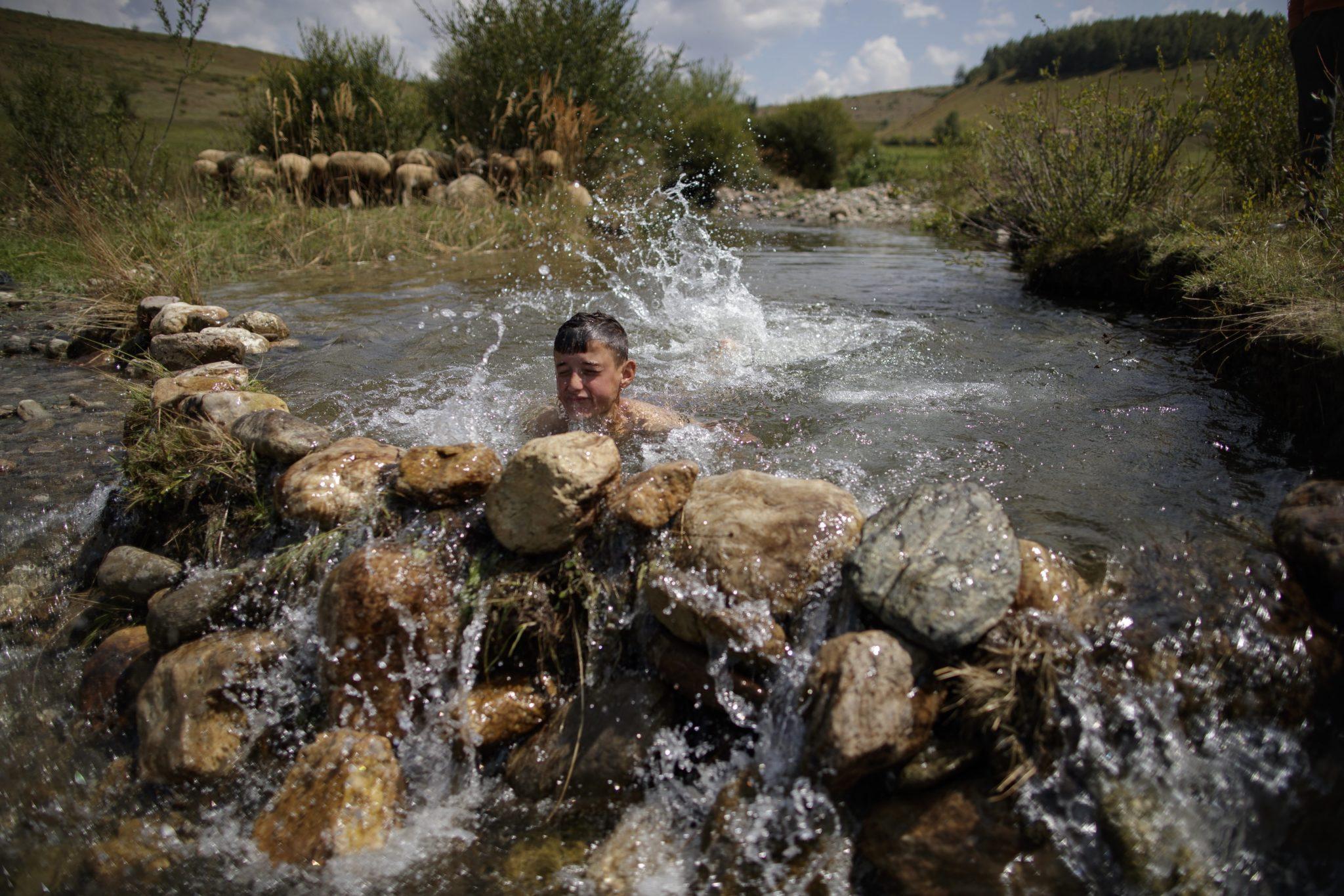 Albaniański chłopiec odświeża się w spiętrzonej części małej wioski w wiosce w Albanii, fot. Valdrin Xhemaj, PAP/EPA
