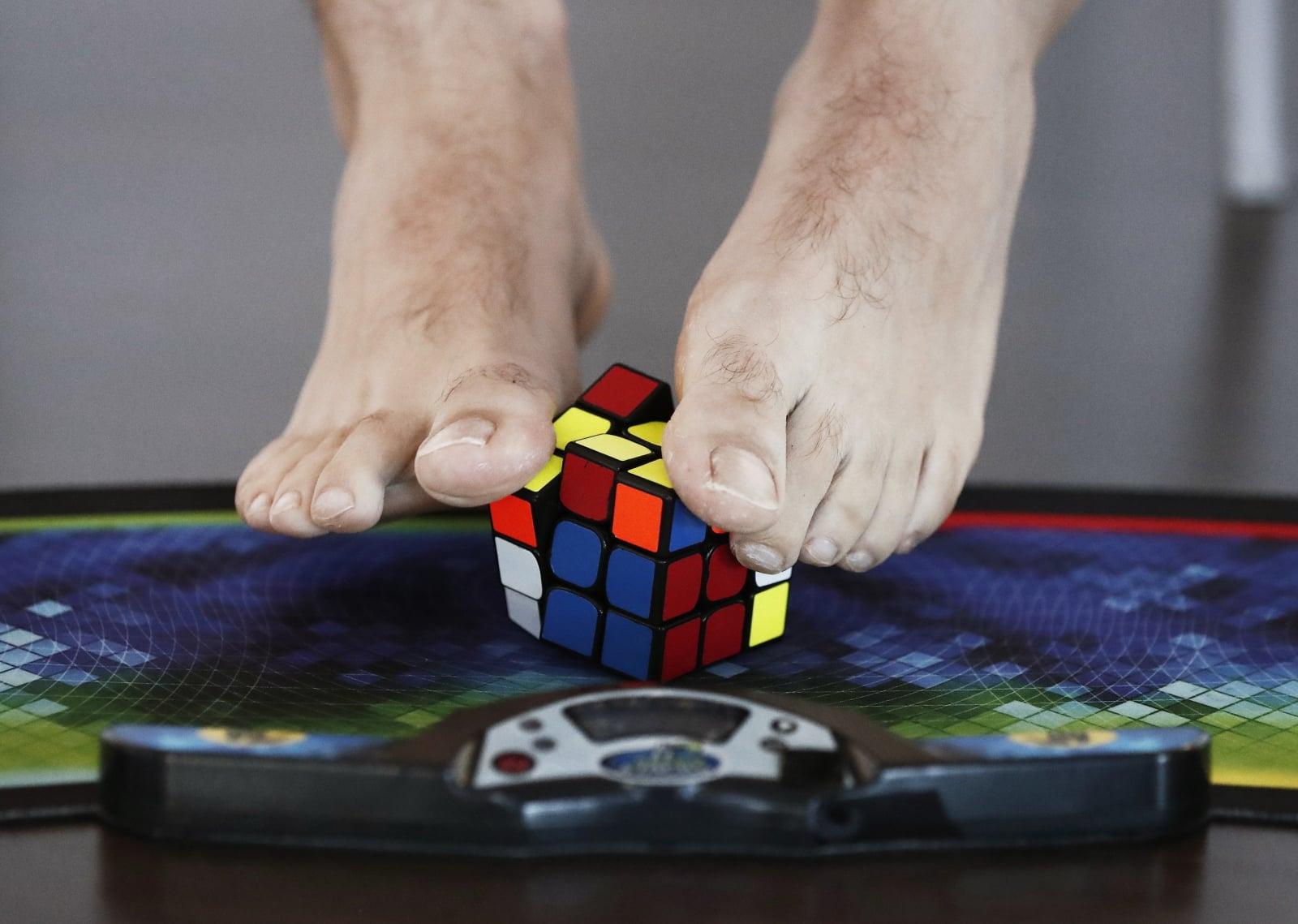 Mężczyzna układający stopami kostkę Rubika podczas 15. edycji Narodowego Konkursu Rubika w Pampelunie, Hiszpania, fot. EPA/JDIGES