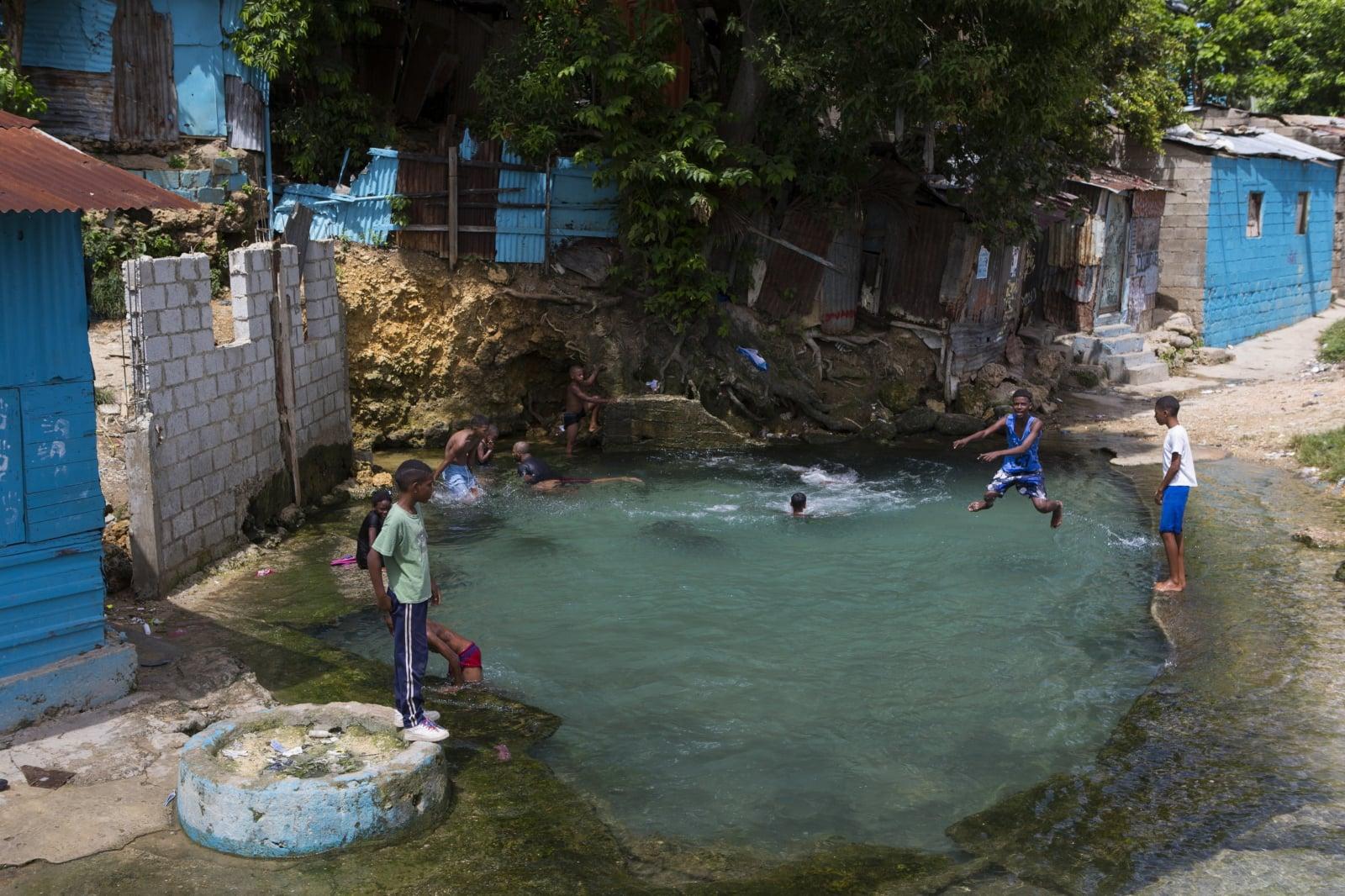 Dzieci bawią się w studni w dzielnicy Gualey, w Santo Domingo, Republika Dominikany,  fot. EPA/Orlando Barria