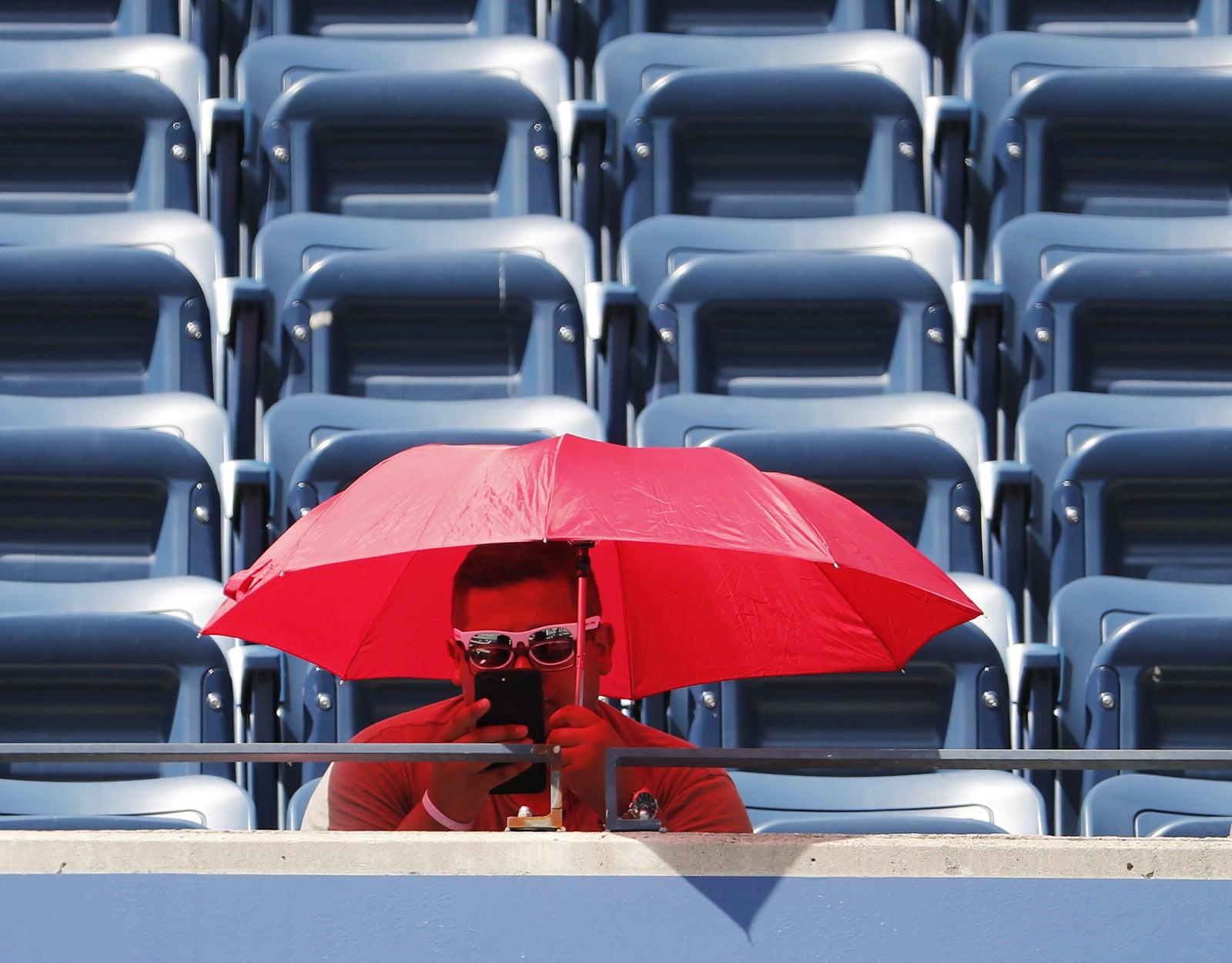 Kibic chroni się przed upałem na trybunach kortu tenisowego Fot. PAP/EPA/JOHN G. MABANGLO