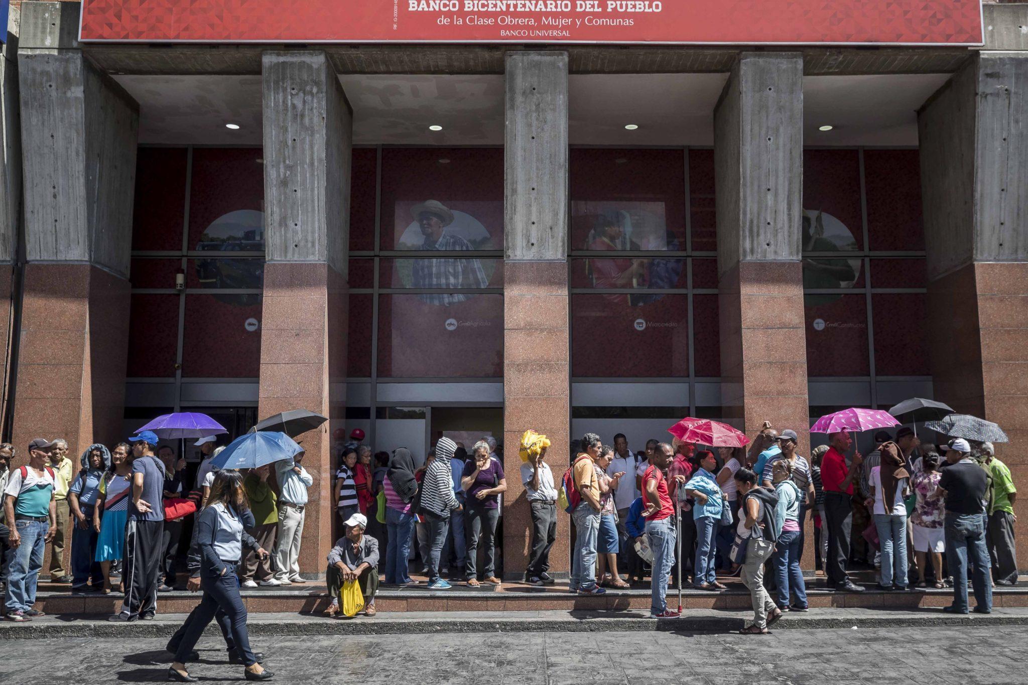 Caracas: ludzie czekają przy wejściu do banku, aby zebrać emerytury. Kryzys ekonomiczny w Wenezueli coraz bardziej się pogłębia. Nie pomaga ręczne sterowanie gospodarką przez prezydenta Maduro, fot. Miguel Gutierrez, PAP/EPA