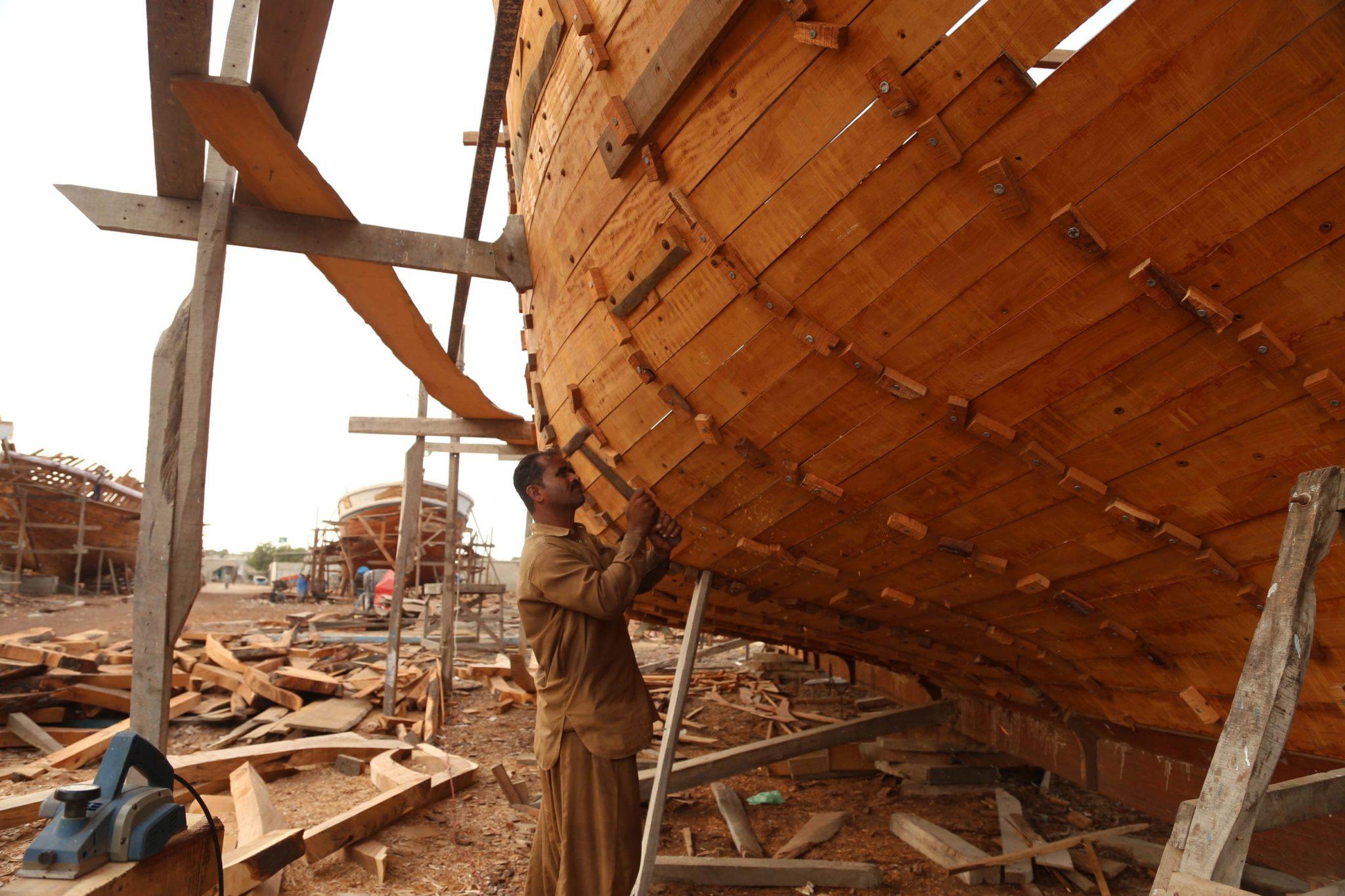 Pakistańscy rzemieślnicy budują łódź w portowym mieście Karaczi w Pakistanie. Stocznia Karachi jest strategicznie położona na skrzyżowaniu Azji Południowej i regionu Zatoki Perskiej, fot. Rehan Khan, PAP/EPA