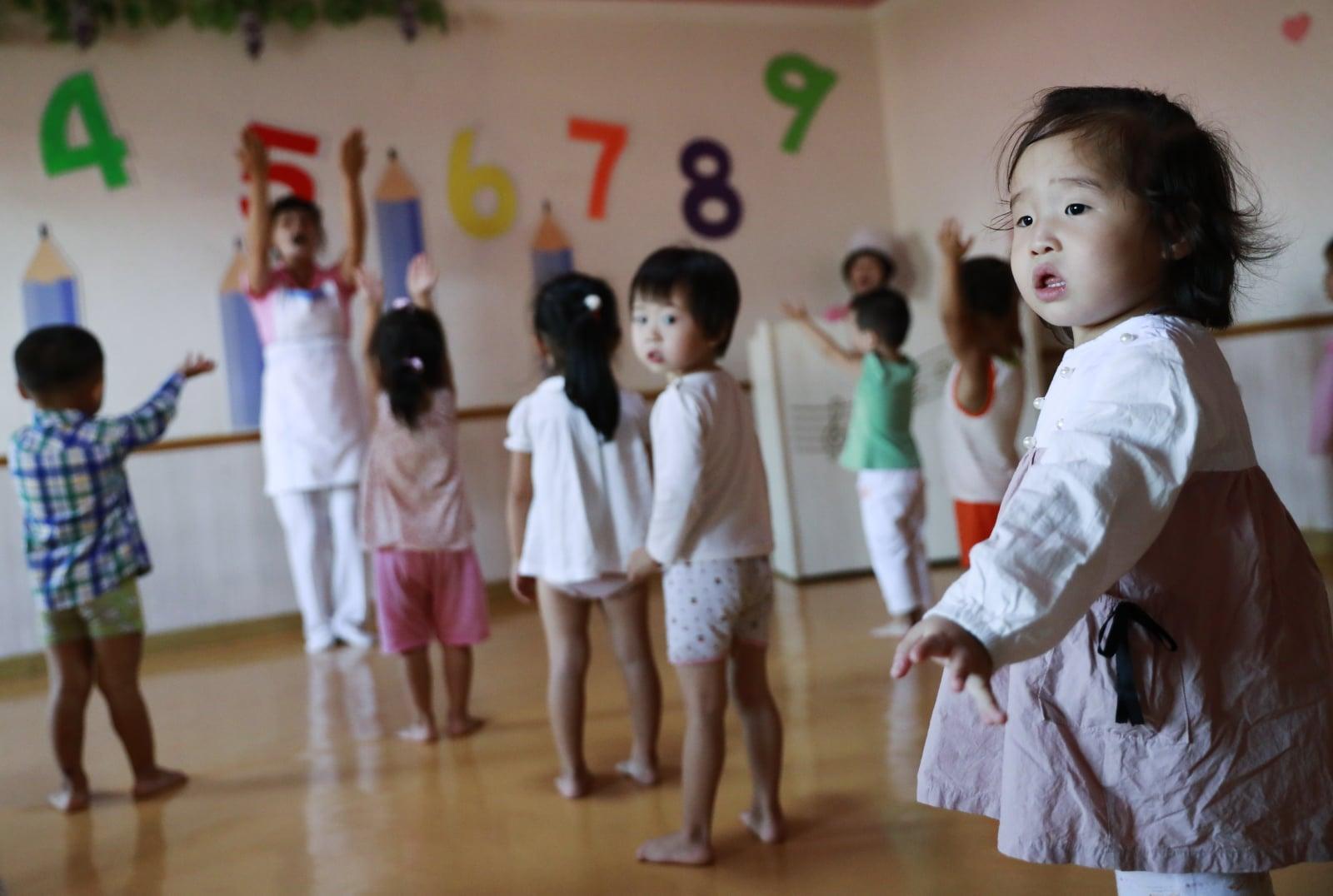 Północnokoreańskie dzieci pracowników fabryki jedwabiu bawią się w zakładowym przedszkolu. Fot. PAP/EPA/HOW HWEE YOUNG