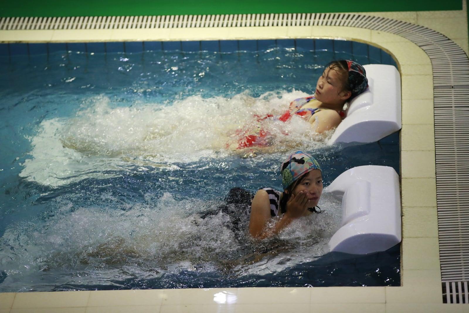 Północnokoreańscy pracownicy fabryki jedwabiu relaksują się w basenie pracowniczym w Pjongjangu. Fot. PAP/EPA/HOW HWEE YOUNG