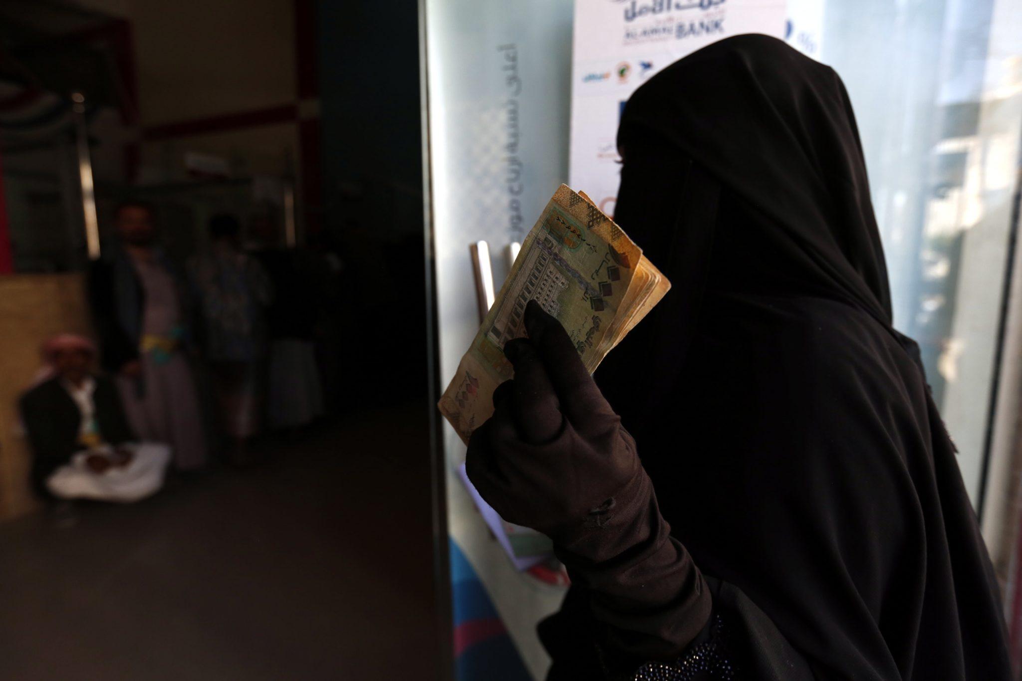 Jemeńska kobieta z najuboższych rodzin dotkniętych konfliktem otrzymuje pomoc UNICEFu, fot. Yahya Arhab, PAP/EPA