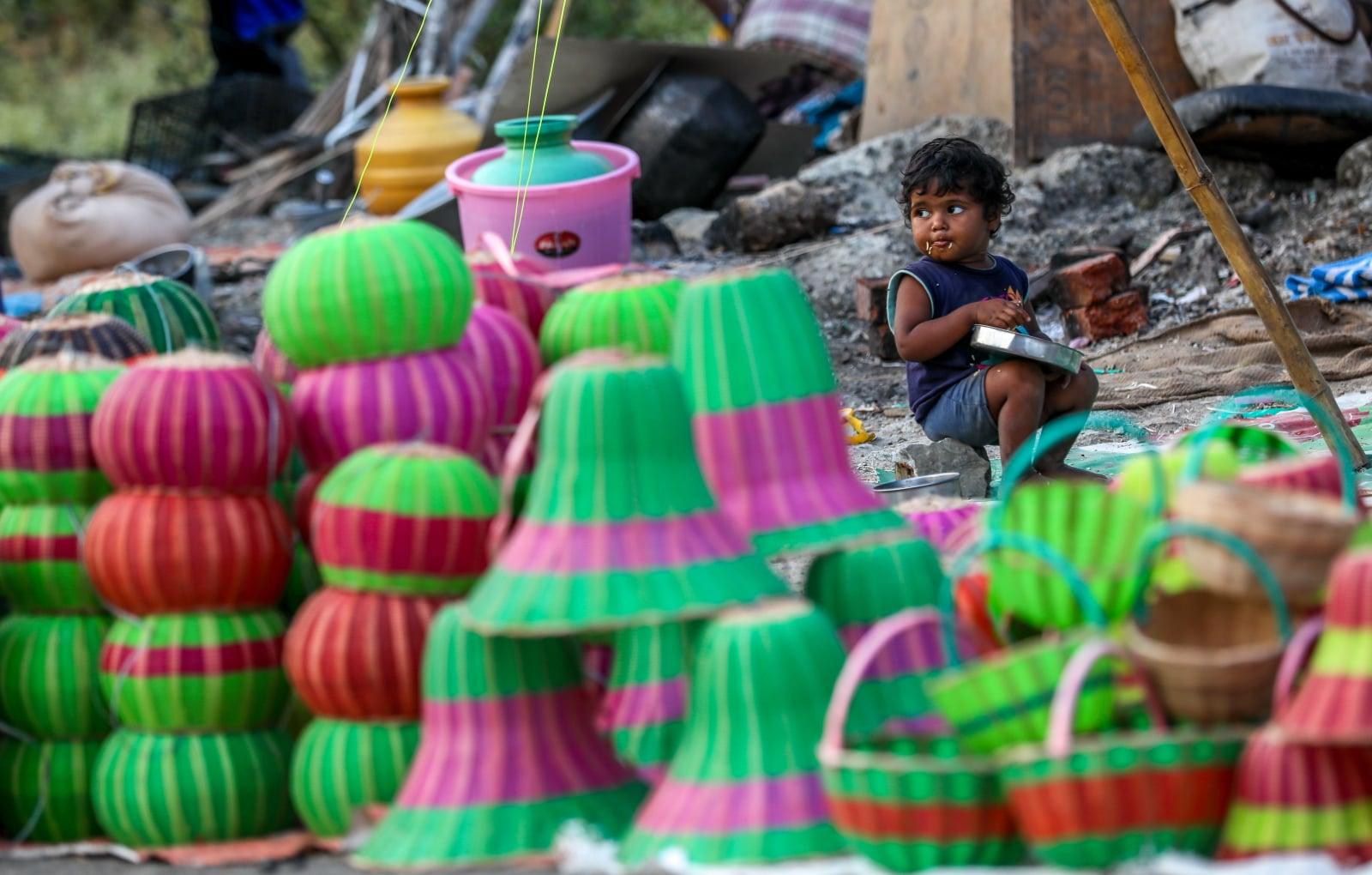 Młode hinduskie dziecko bawi się przy lampionach ustawionych na święto Diwali. Fot. PAP/EPA/DIVYAKANT SOLANKI