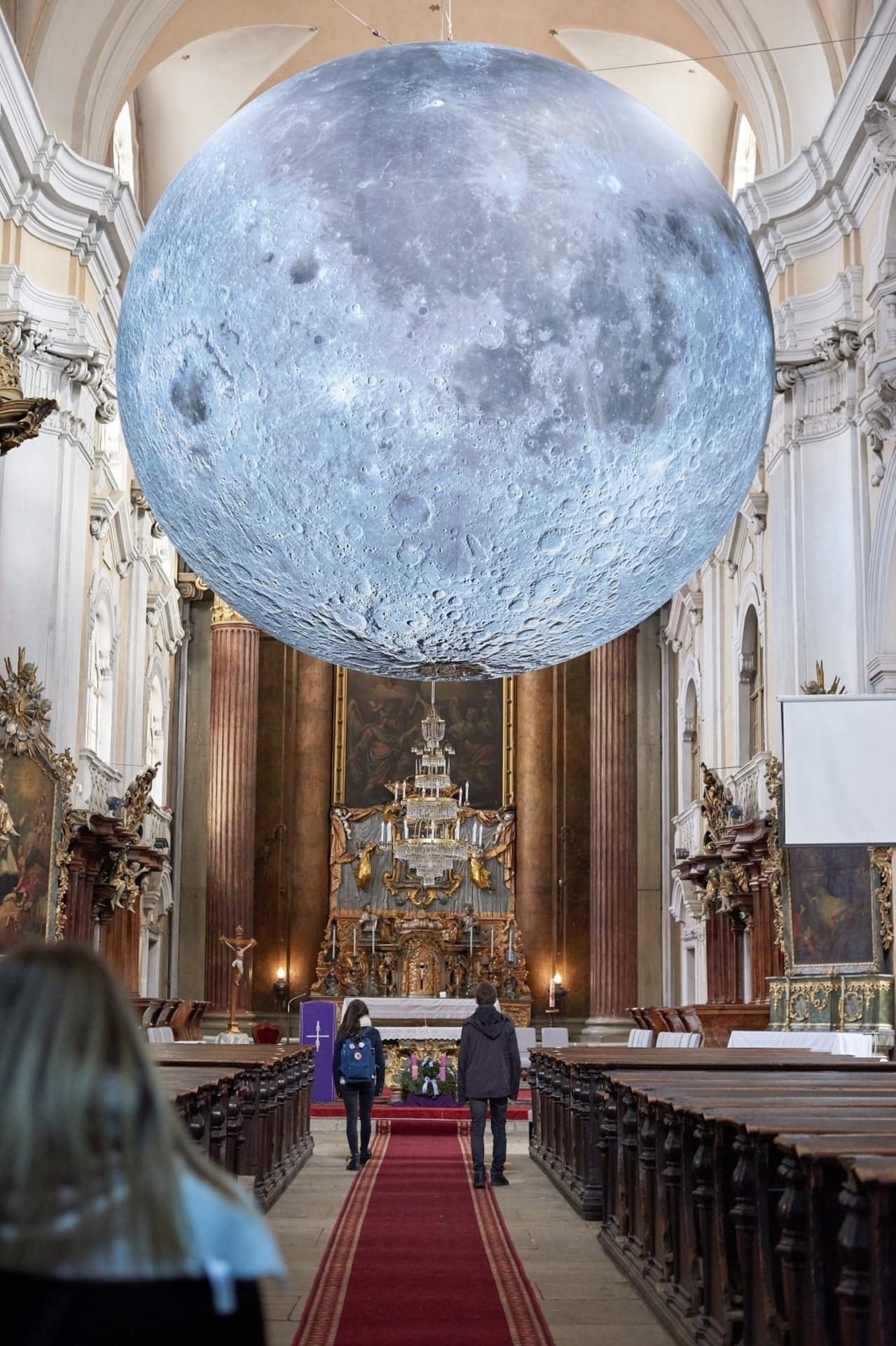Ludzie oglądają wystawę nazwaną Muzeum Księżyca autorstwa Luke'a Jerrama w kościele pijarów Cluj-Napoca w Rumunii. Fot. PAP/EPA/ISTVAN BIRO