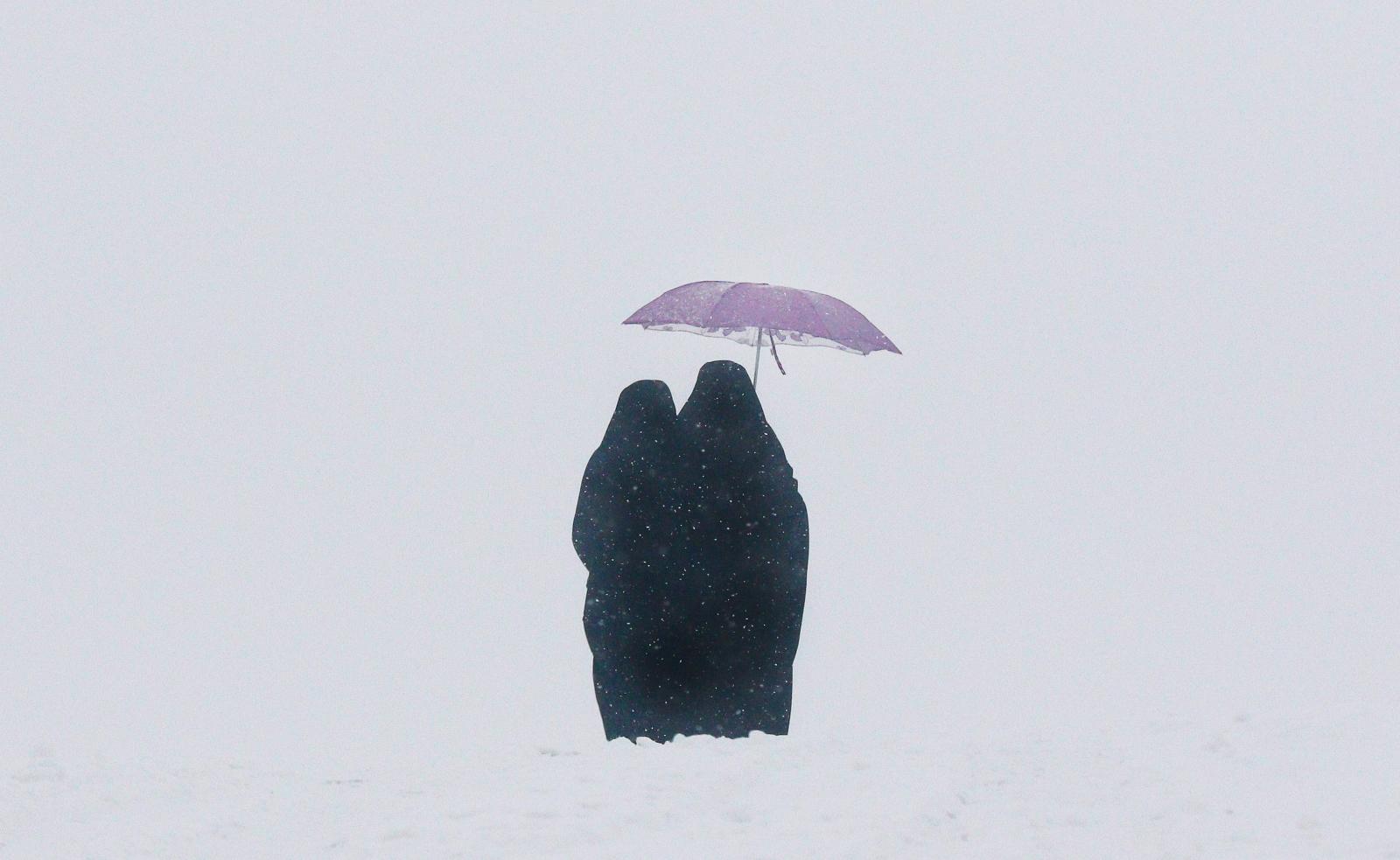 Kobiety spacerują w czasie opadów śniegu na przedmieściach Kabulu w Afganistanie. Fot. PAP/EPA/HEDAYATULLAH AMID