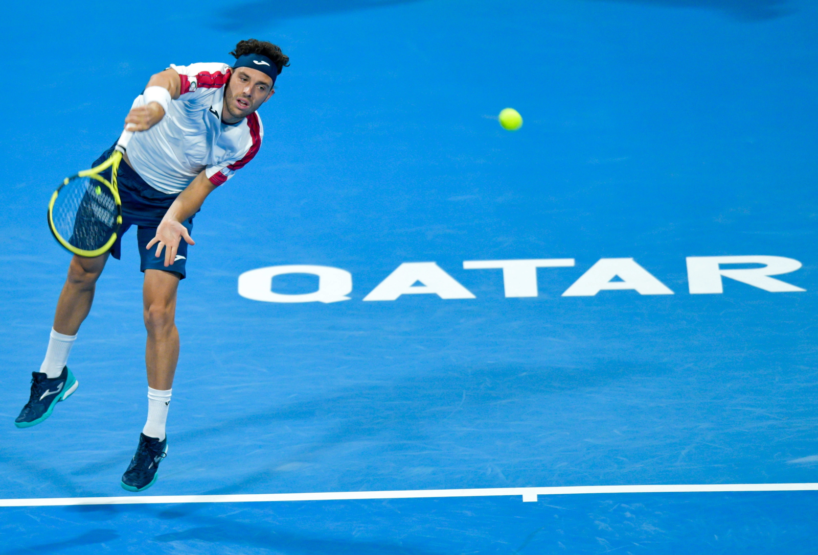 Włoch Marco Cecchinato w akcji przeciwko Tomasowi Berdyczowi z Czech podczas półfinałowego meczu turnieju ATP Qatar Open Tennis w Doha, Katar.  Fot. PAP/EPA/NOUSHAD THEKKAYIL