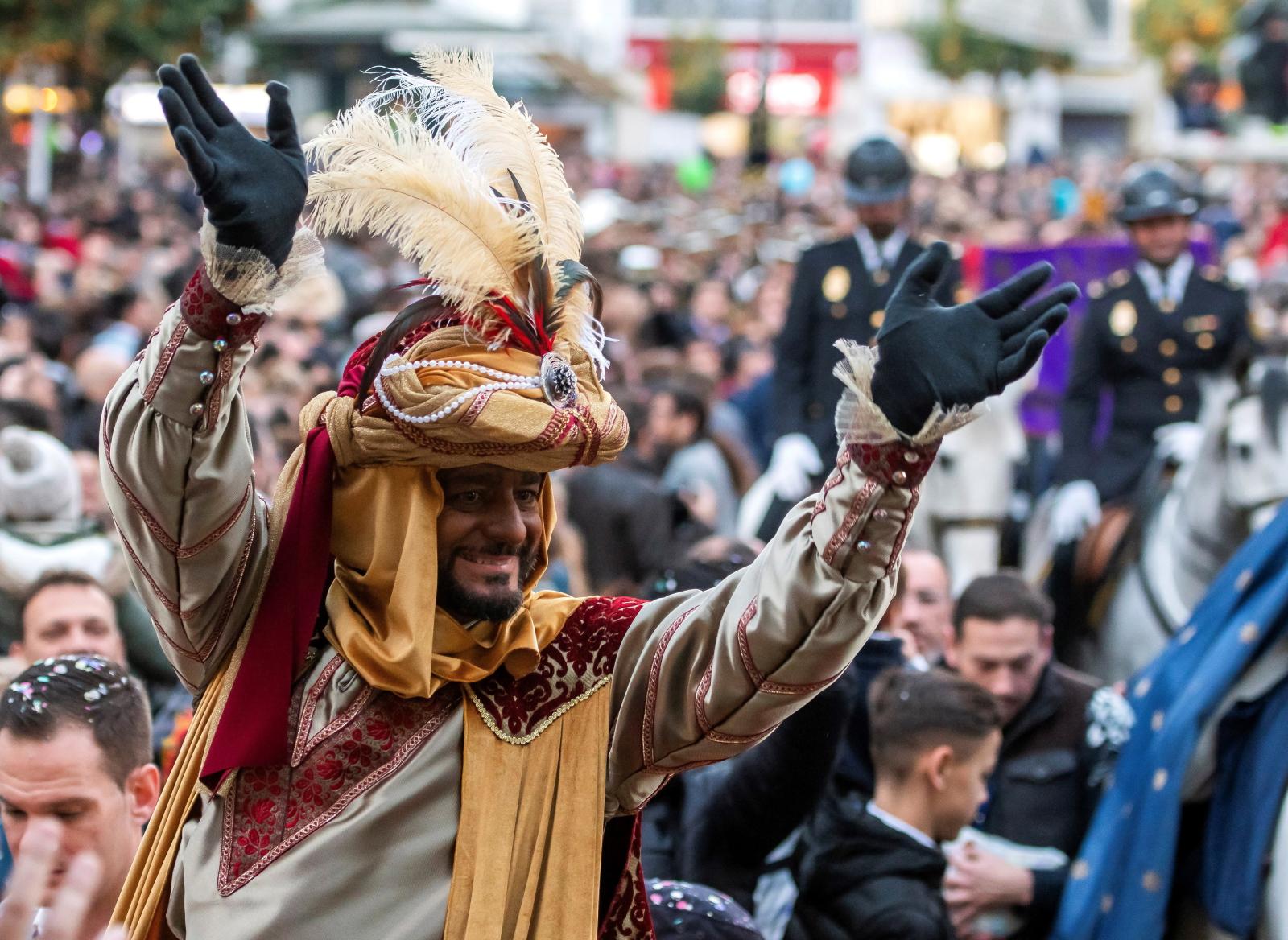Mężczyźni przebrani za trzech mędrców pozdrawiają uczestników parady w hiszpańskiej Sewilli. Fot. PAP/ EPA/Raul Caro