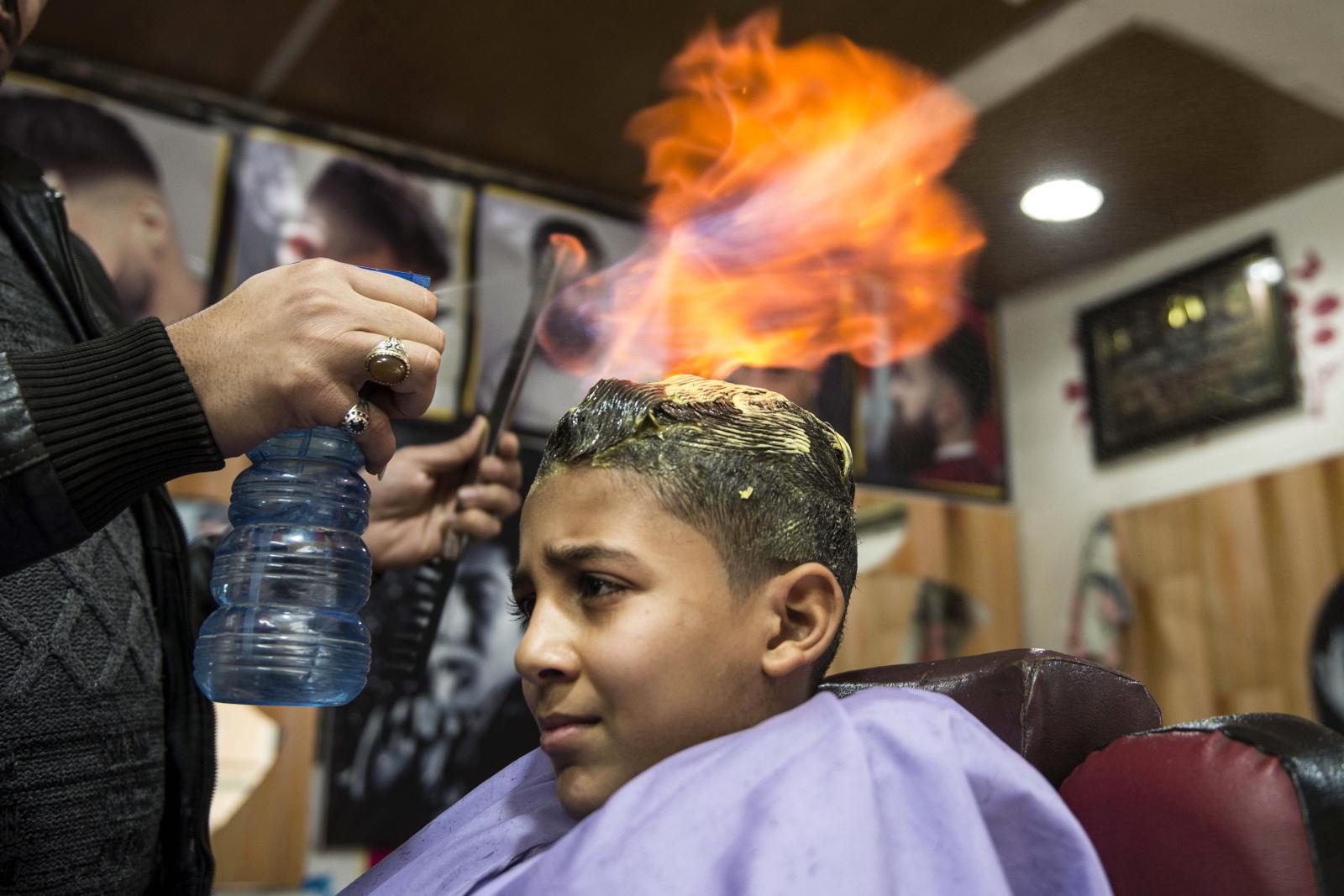Egipski fryzjer używa ognia do stylizacji włosów. Fot. PAP/EPA/MOHAMED HOSSAM
