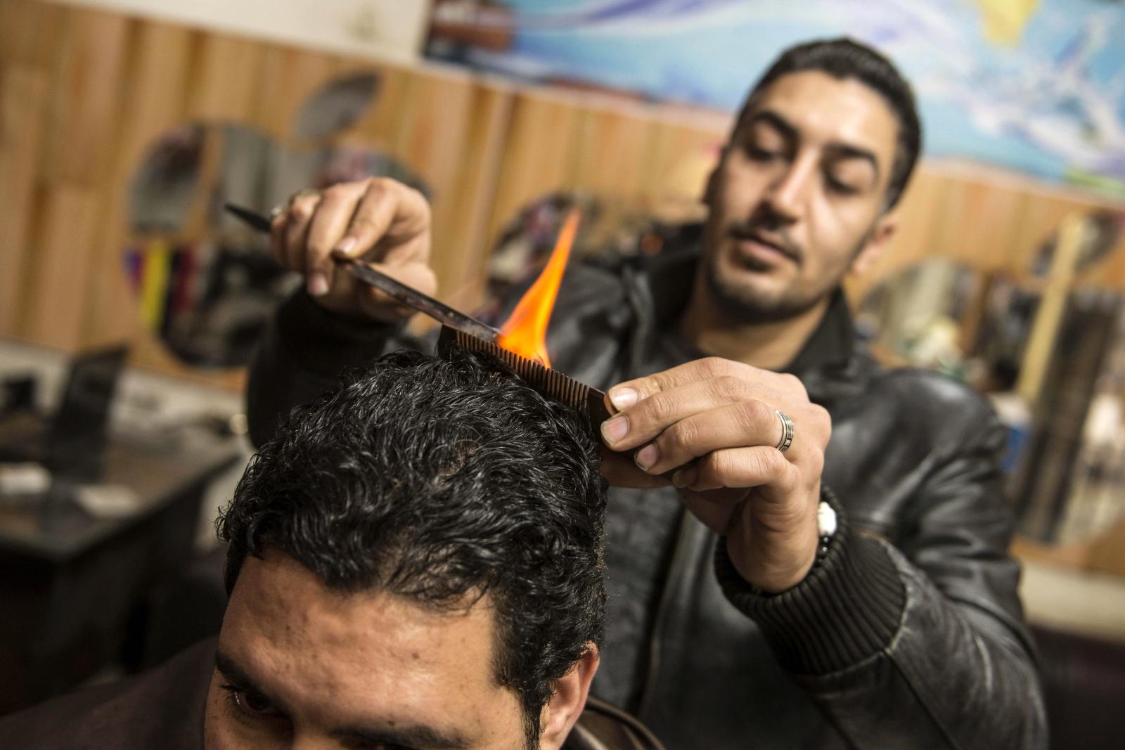 Egipski fryzjer stylizuje włosy używając ognia. Fot. PAP/EPA/MOHAMED HOSSAM