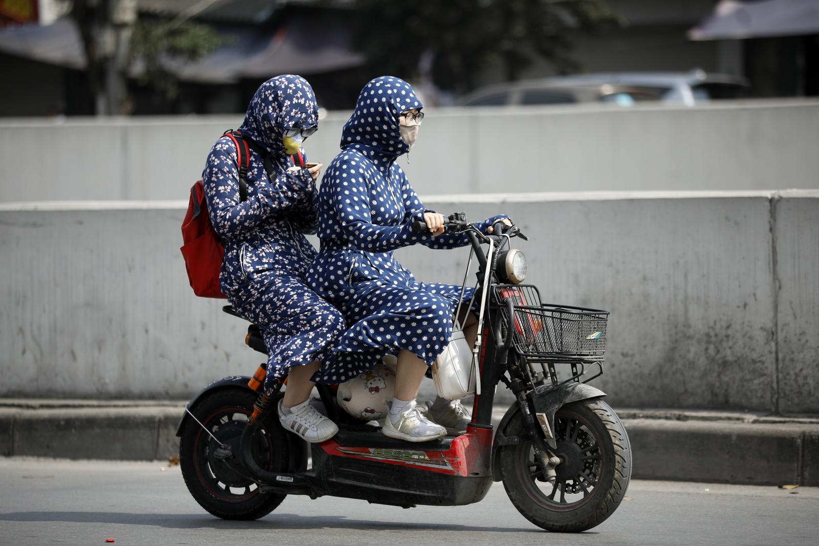 Ludzie specjalnie ubrani, by chronić się przed upałem na ulicach WIetnamu/EPA/LUONG THAI LINH