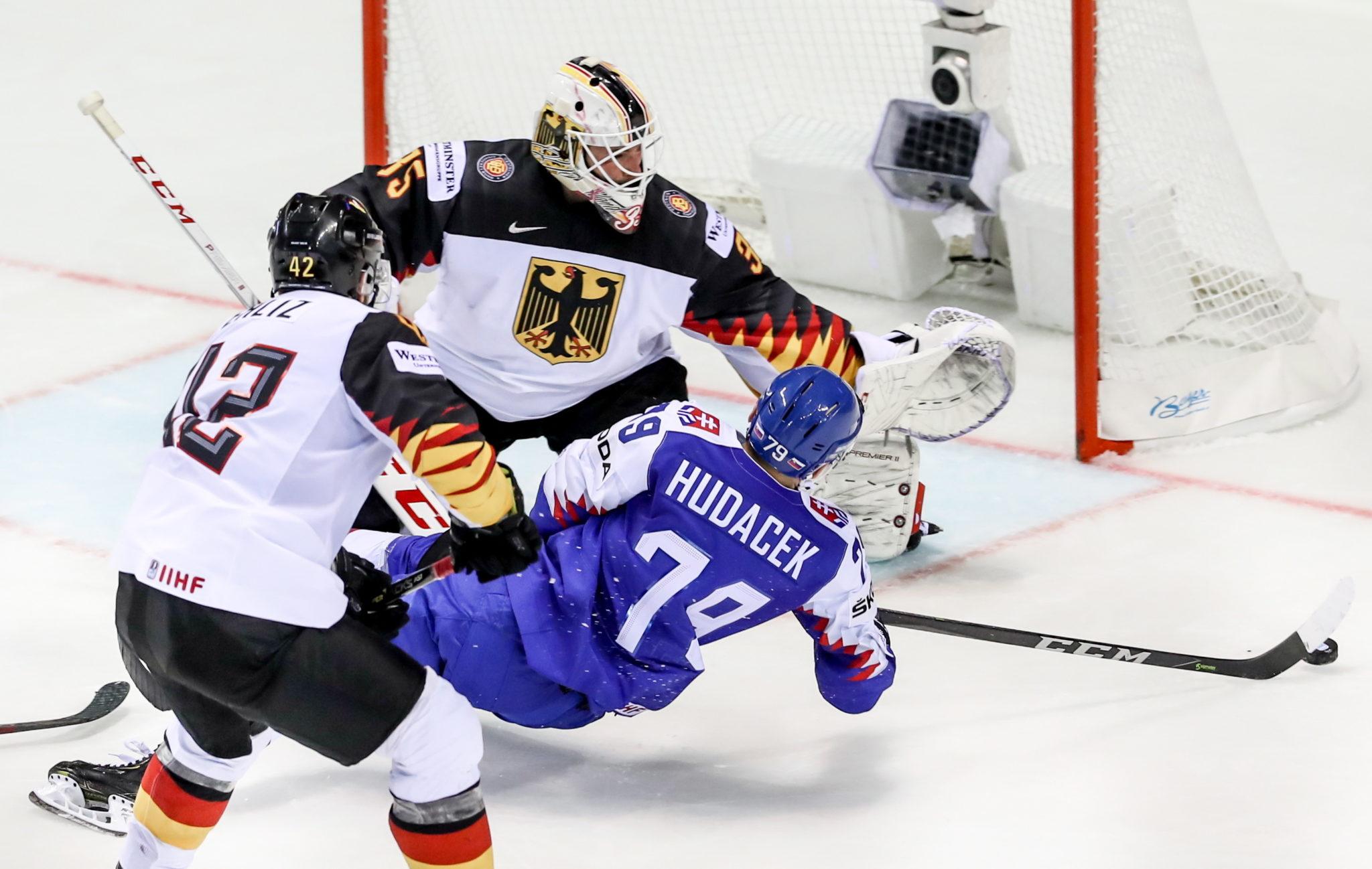 Słowacja, Koszyce: Libor Hudacek ze Słowacji w akcji przeciwko bramkarzowi Matthiasowi Niederbergerowi z Niemiec podczas grupy Mistrzostw Świata IIHF, fot. MARTIN DIVISEK, PAP/EPA.