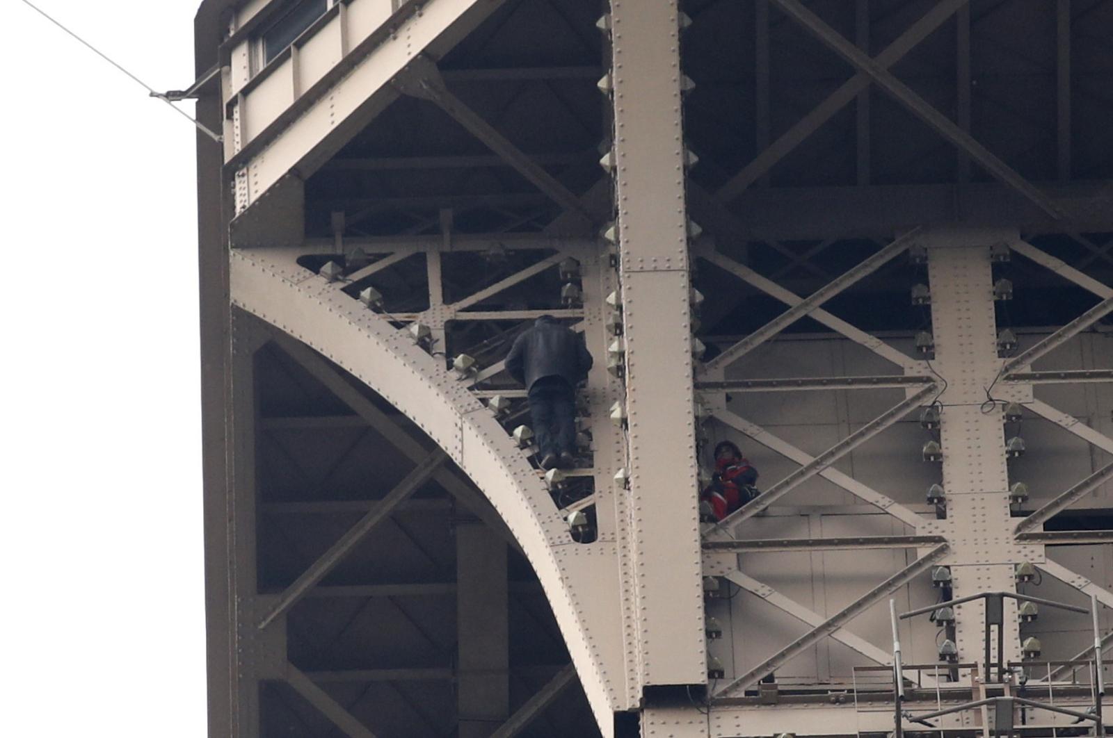 Mężczyzna wspiął się na wieżę Eiffla, próbuje powstrzymać go strażak. Fot. PAP/EPA/YOAN VALAT