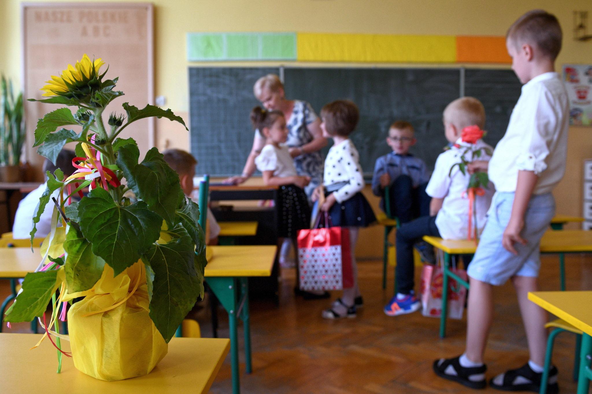 Czelatyce, uczniowie wiejskiej Szkoły Podstawowej wręczają kwiaty nauczycielom podczas, fot. Darek Delmanowicz, PAP