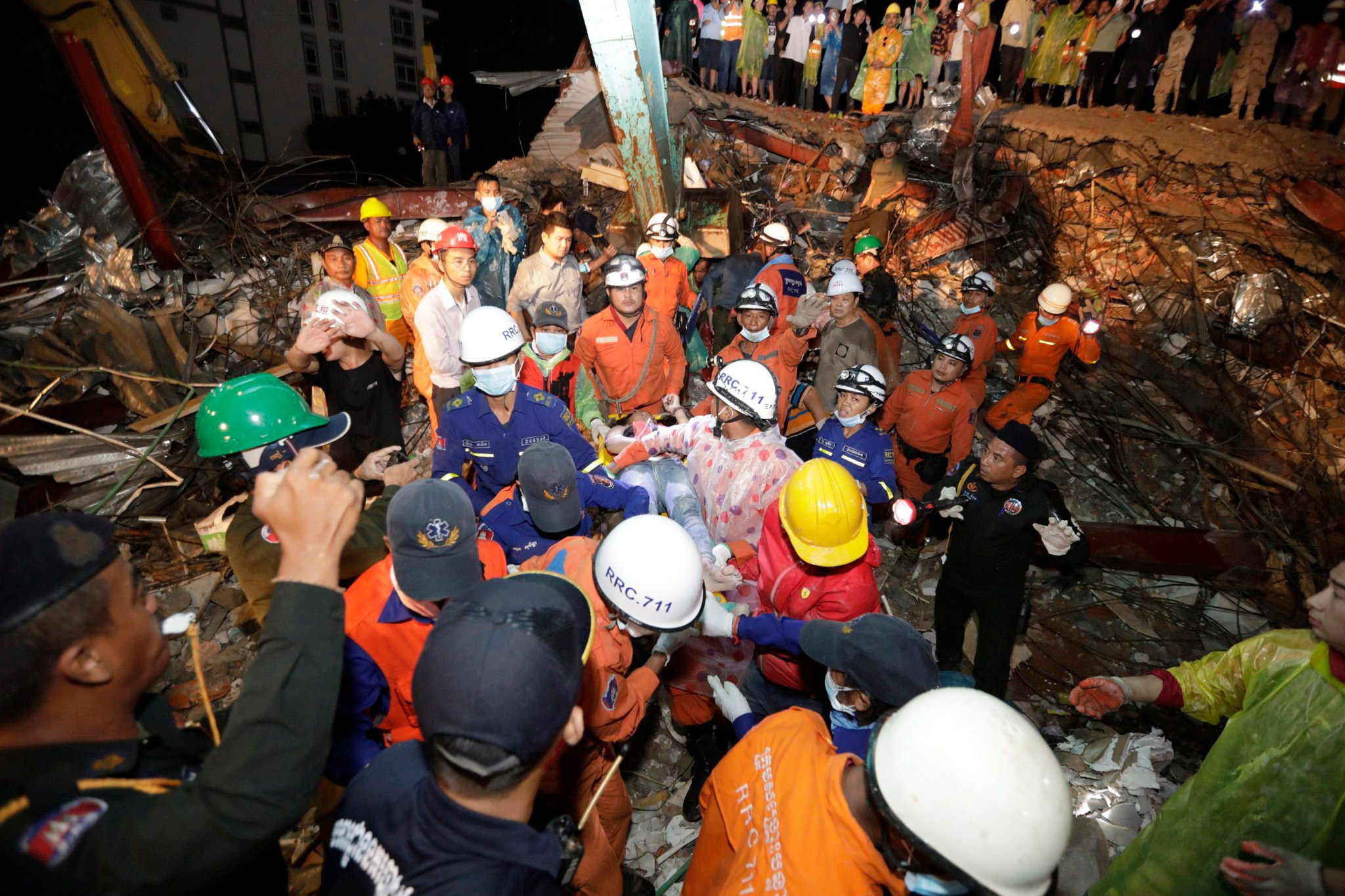 epaselect epa07666866 A Cambodian rescue team carries an injured worker at the site of a collapsed building at a construction site in Preah Sihanouk province, Cambodia, 23 June 2019. A new seven-story building owned by a Chinese company, collapsed in Preah Sihanouk province, killing at least 15 workers and leaving 24 workers injured.  EPA/MAK REMISSA  Dostawca: PAP/EPA.