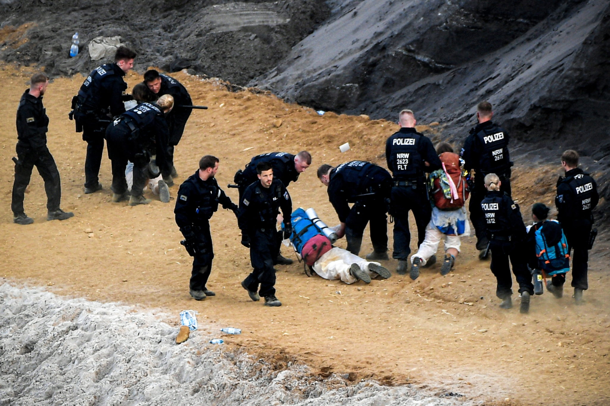 epa07667113 Activists taking part in the 'Ende Gelaende' protest initiative face a police cordon in a pit in the Rhenish coal mining area around Garzweiler in Jackerath, Germany, 22 June 2019. Several thousand protestors are expected at the 'Ende Gelaende' event from 19 through 24 June 2019.  EPA/SASCHA STEINBACH  Dostawca: PAP/EPA.