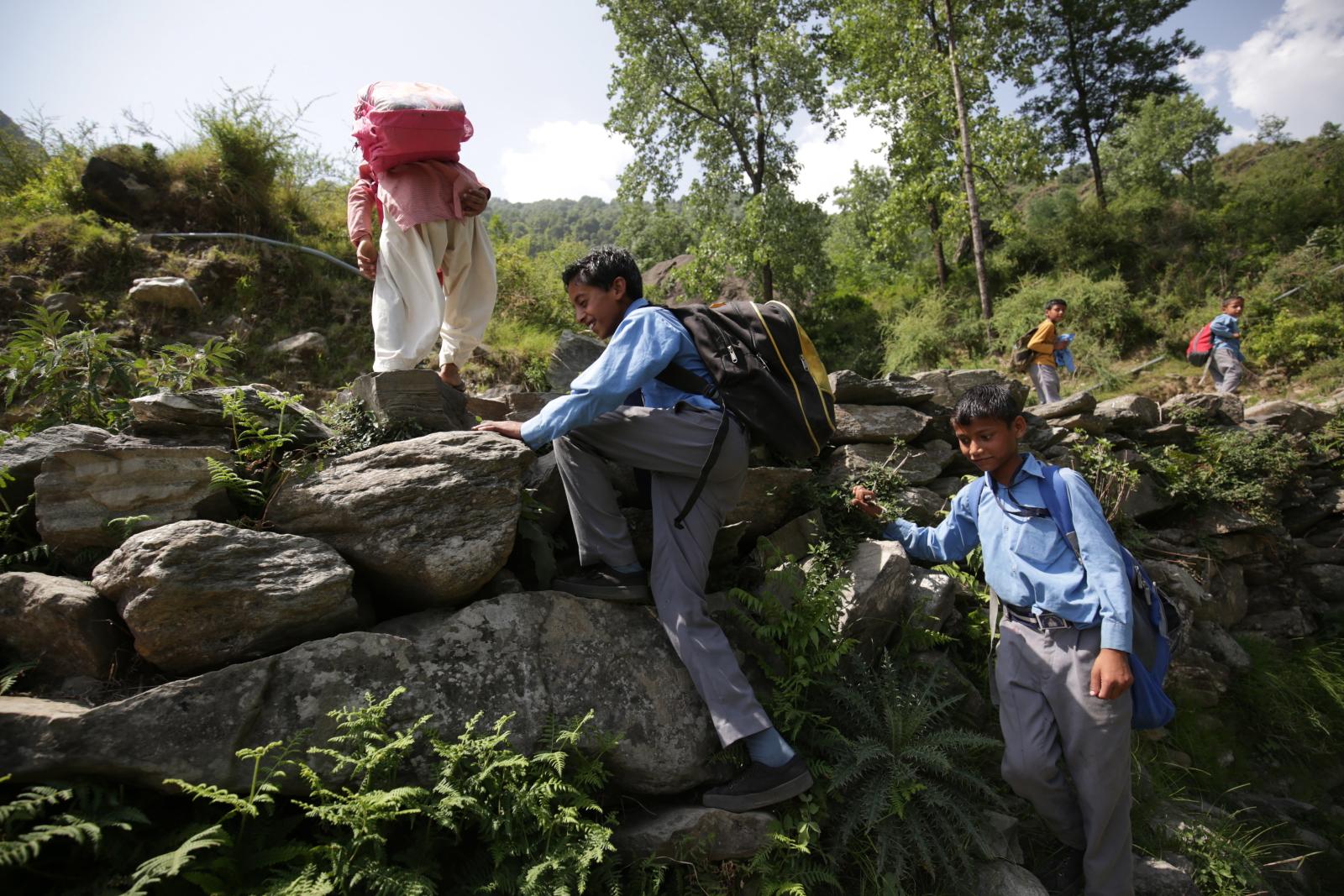 Indyjskie dzieci wspinają się na skały wracając ze szkoły. Fot. PAP/EPA/RAMINDER PAL SINGH