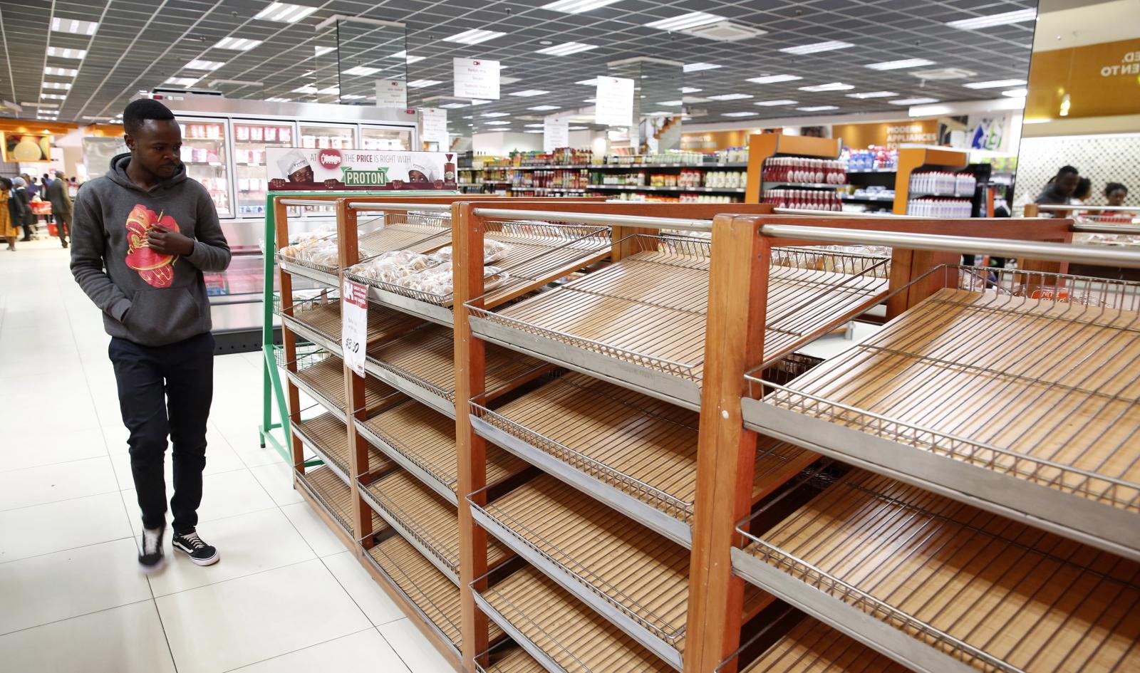 Klient przechodzi obok pustych półek z chlebem w jednym z największych supermarketów w Harare, Zimbabwe. W całym kraju panuje kryzys pszenicy. Fot. PA/AARON UFUMELI