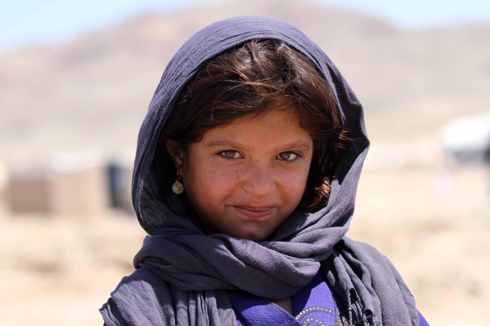 Afgańska dziewczyna, która została wewnętrznie przesiedlona z powodu konfliktu i katastrofy, pozuje do zdjęcia w swoim tymczasowym schronieniu zapewnionym przez Wysokiego Komisarza Narodów Zjednoczonych ds. Uchodźców (UNHCR) na obrzeżach Herat, Afganistan. Fot.  EPA/JALIL REZAYEE